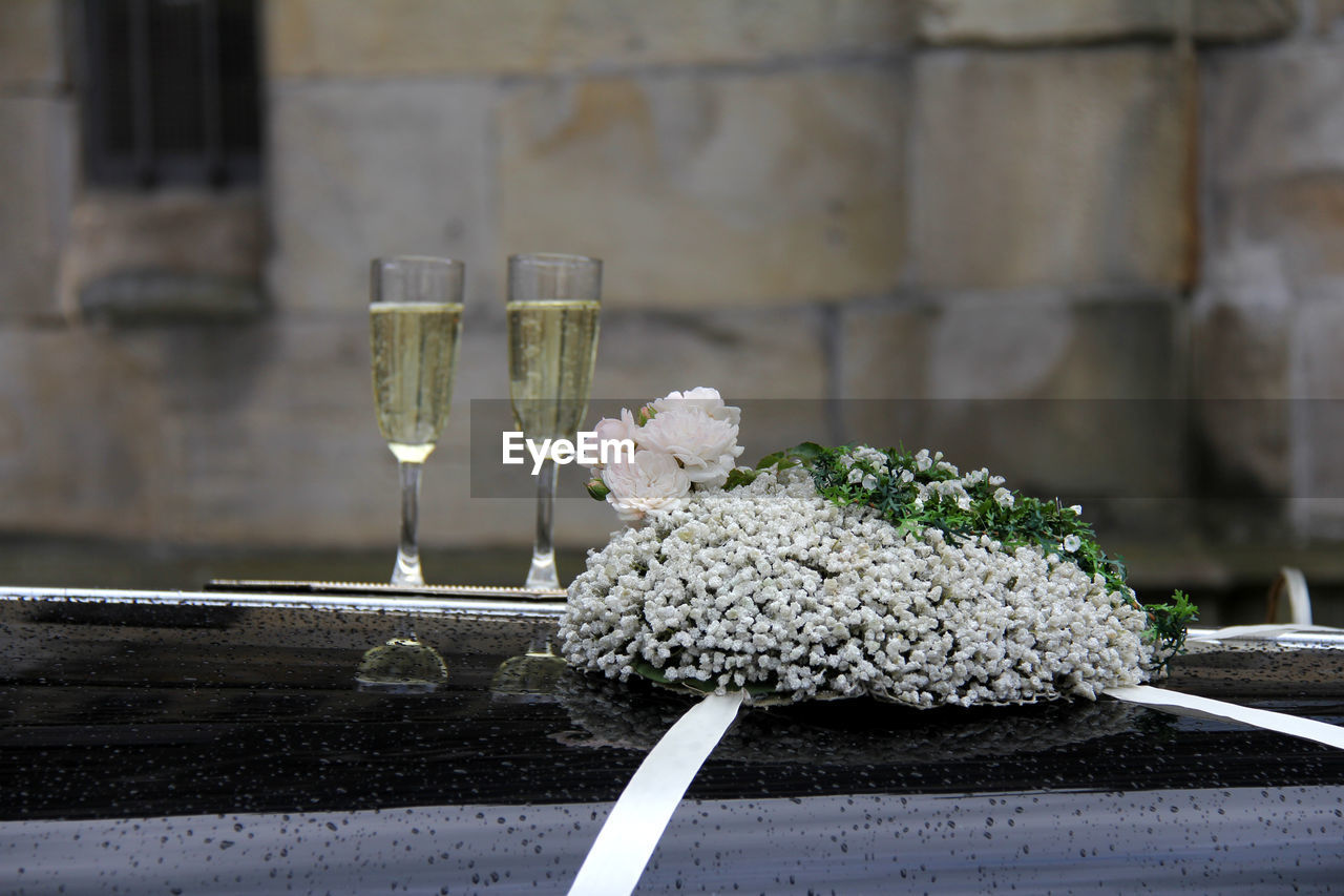 Close-up of champagne and flowers on wedding car