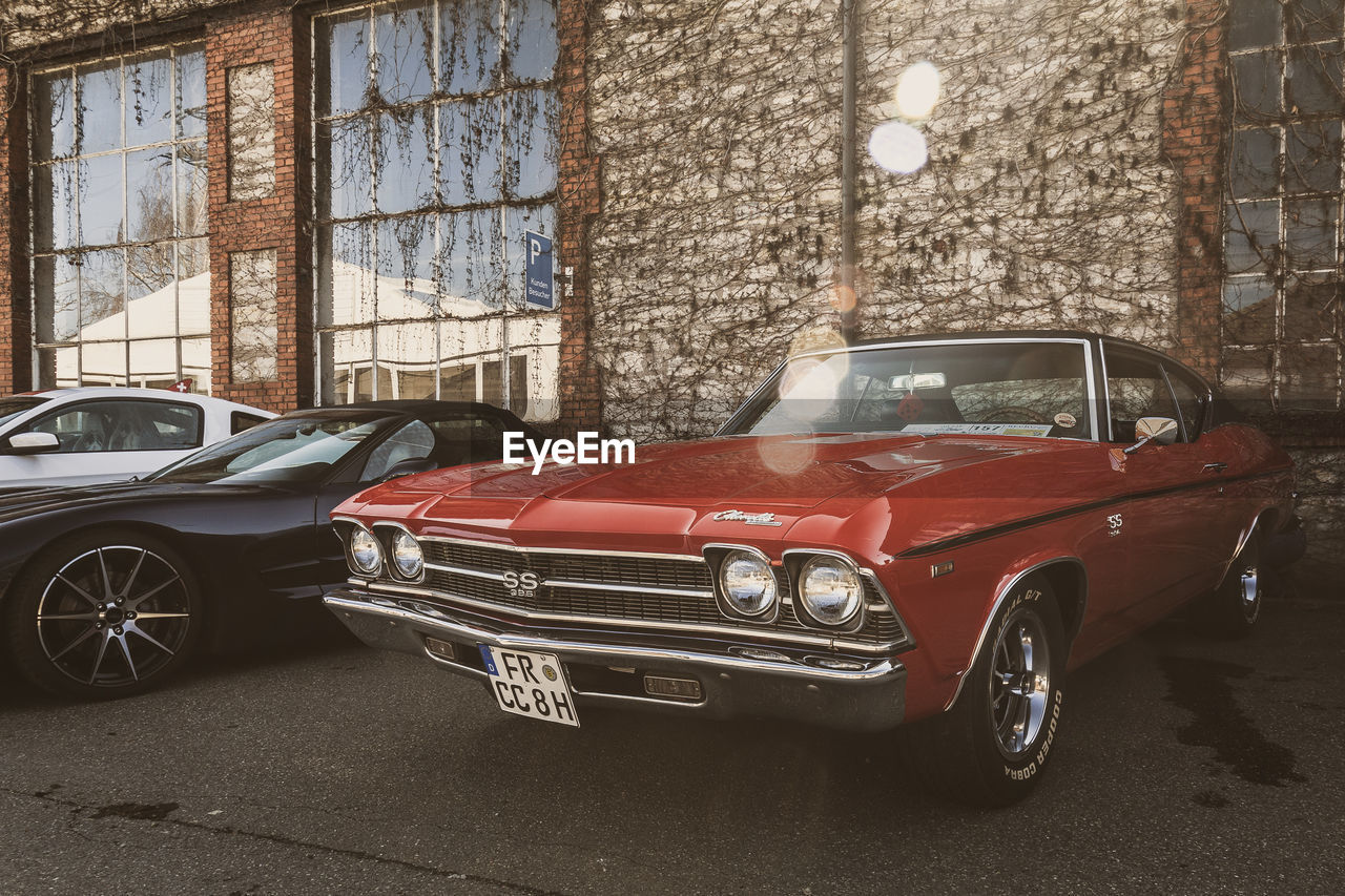 car, motor vehicle, mode of transportation, land vehicle, transportation, architecture, building exterior, vintage car, built structure, city, retro styled, stationary, no people, day, red, glass - material, street, outdoors, parking, luxury, garage