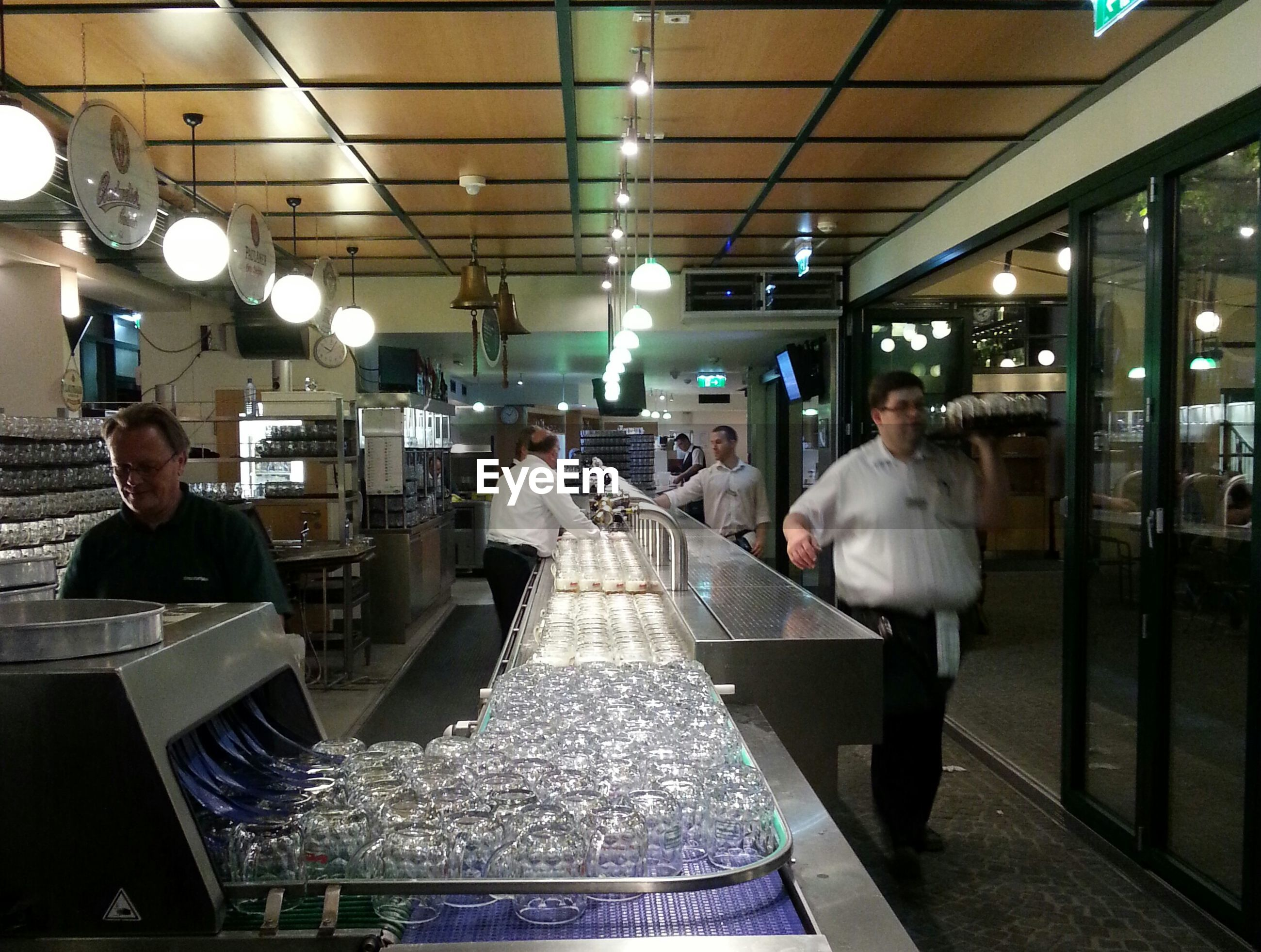 indoors, lifestyles, sitting, restaurant, food and drink, table, leisure activity, men, person, holding, glass - material, reflection, architecture, casual clothing, chair, illuminated, incidental people
