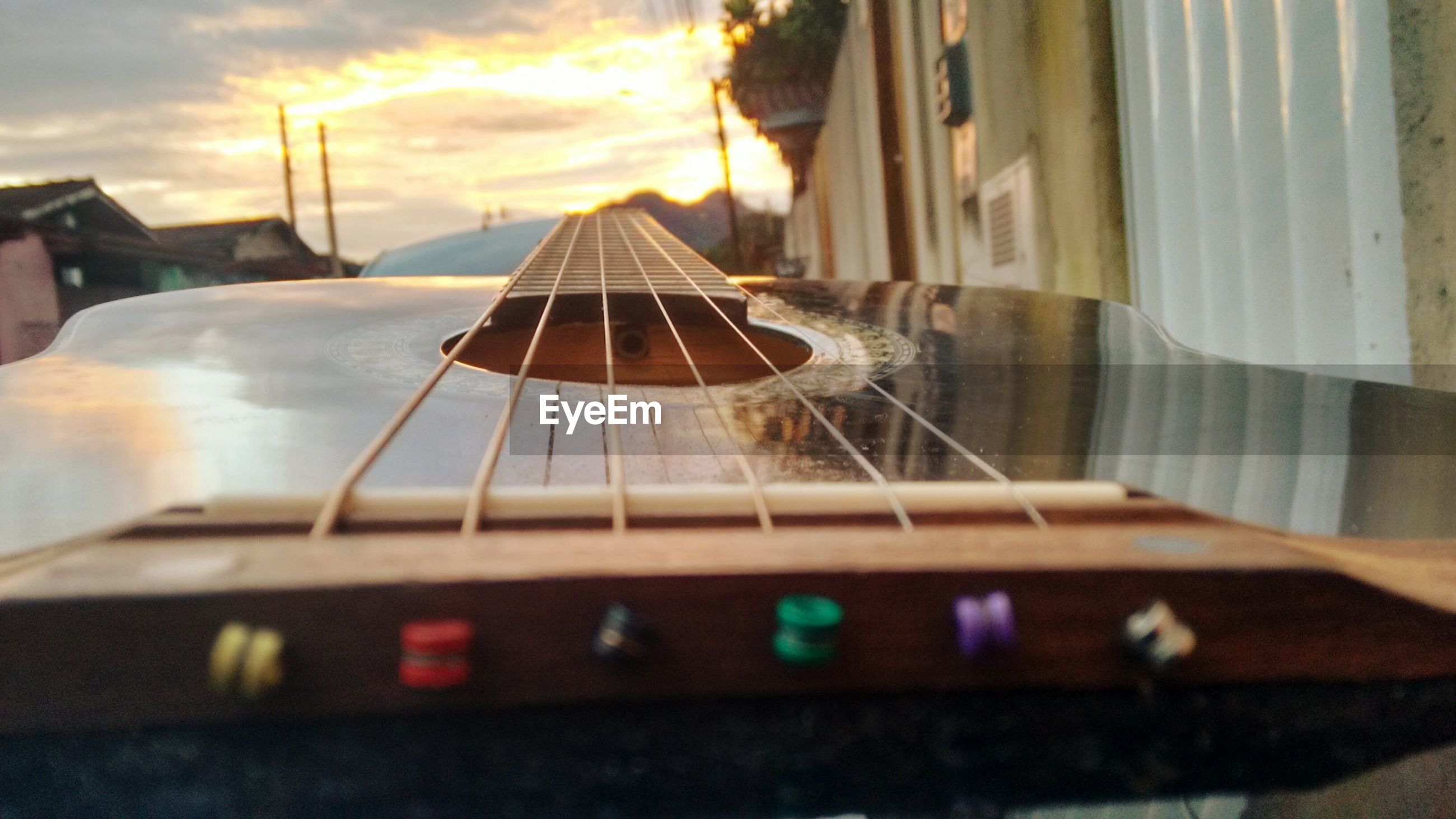 Close-up of guitar against sky during sunset