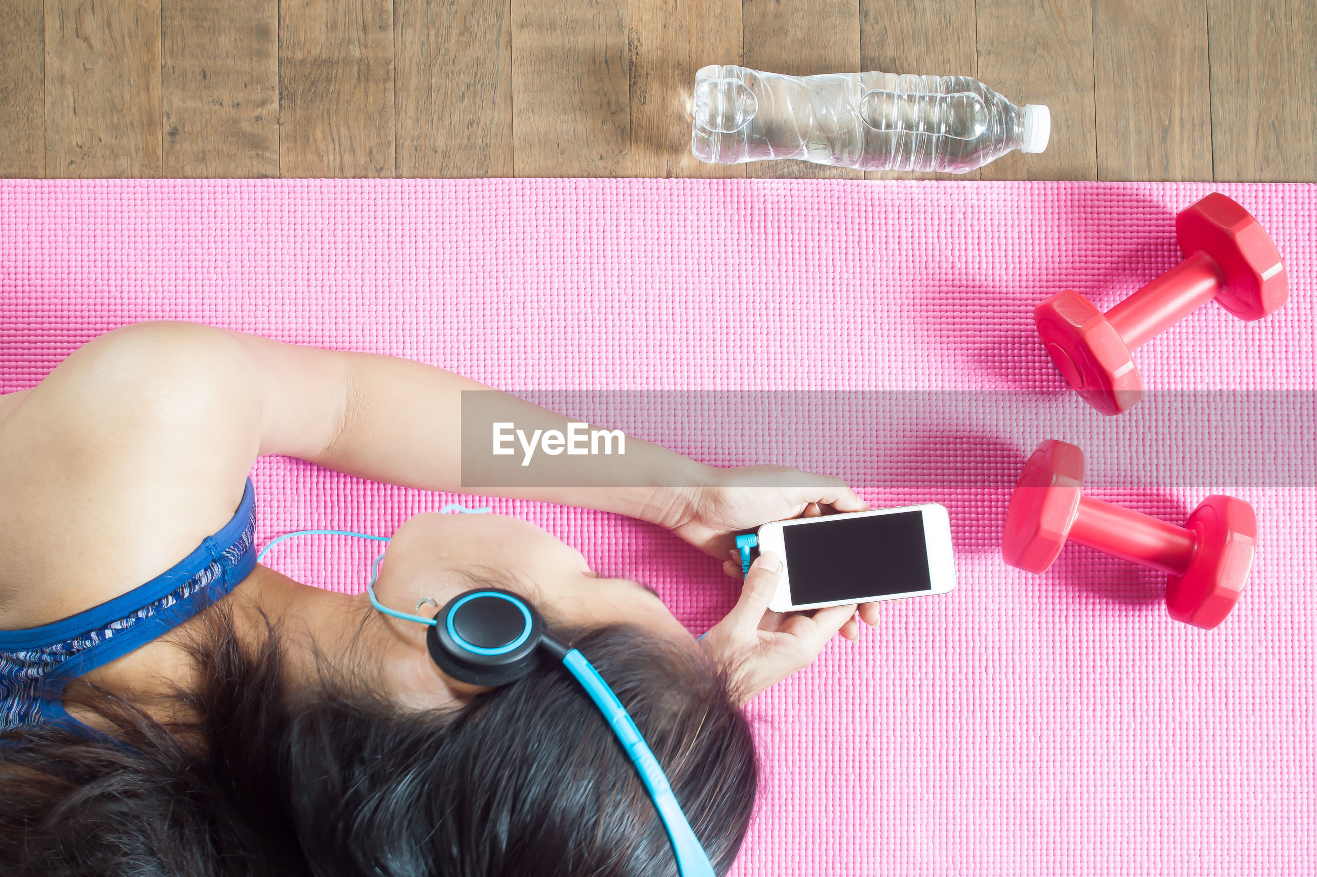 High angle view of woman using mobile phone on exercise mat
