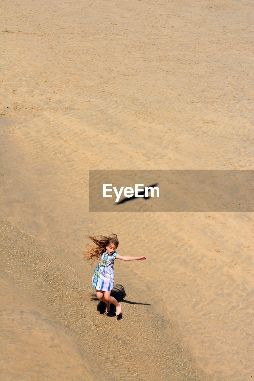 High angle view of girl jumping on beach