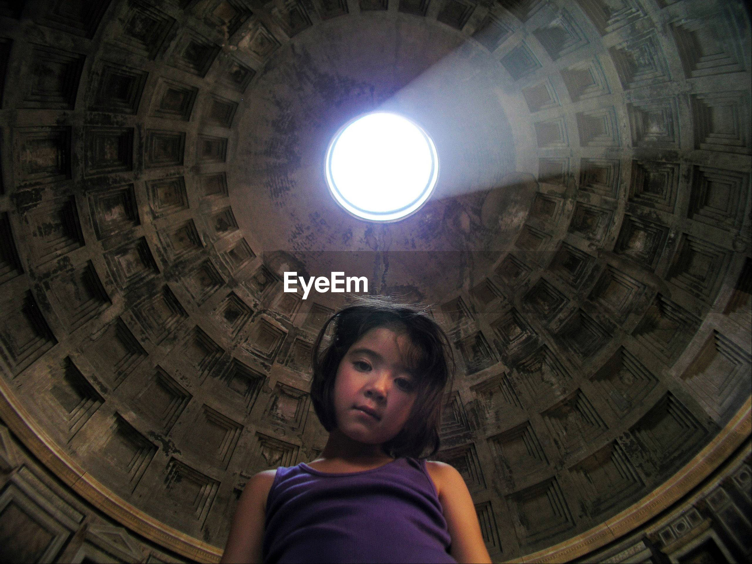 Portrait of cute girl against ceiling of cathedral