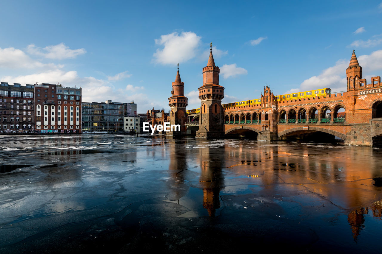 Oberbaum Bridge Over Frozen Spree River Against Sky
