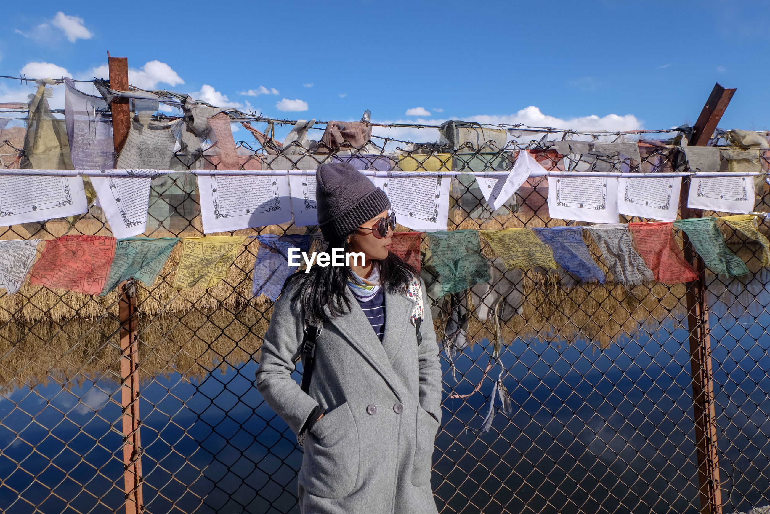 Woman wearing warm clothing while standing against fence and prayer flags