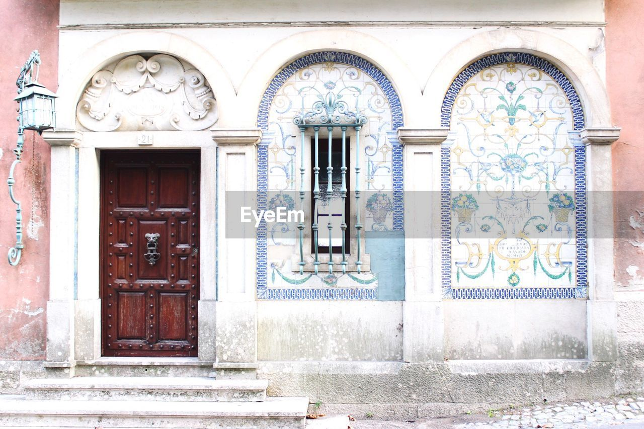 architecture, door, entrance, built structure, window, building exterior, no people, building, art and craft, day, arch, closed, human representation, craft, representation, ornate, outdoors, creativity, female likeness, the past, bas relief