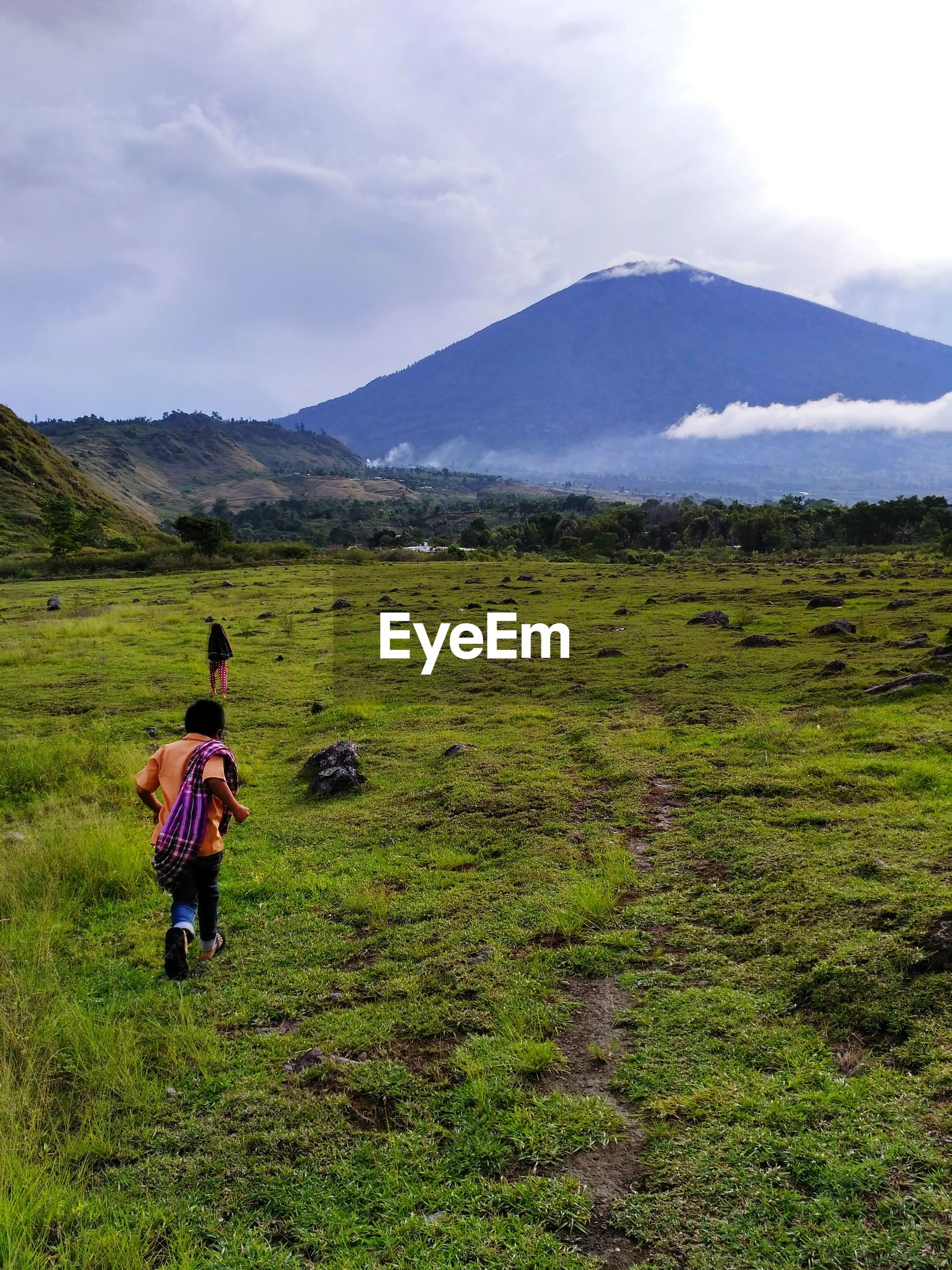 Rear view of children walking on grassy field against sky
