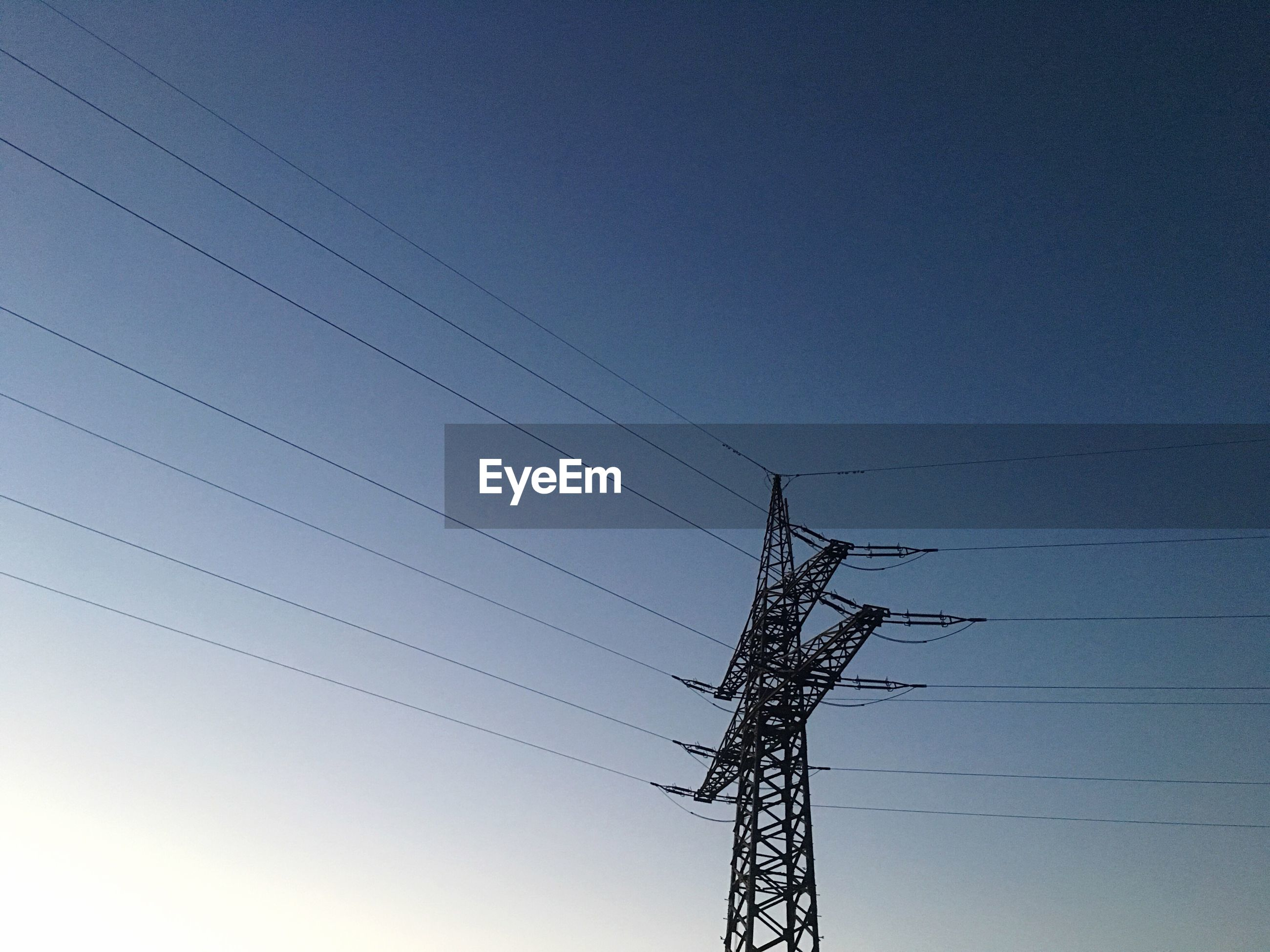 Low angle view of silhouette electricity pylon against clear blue sky