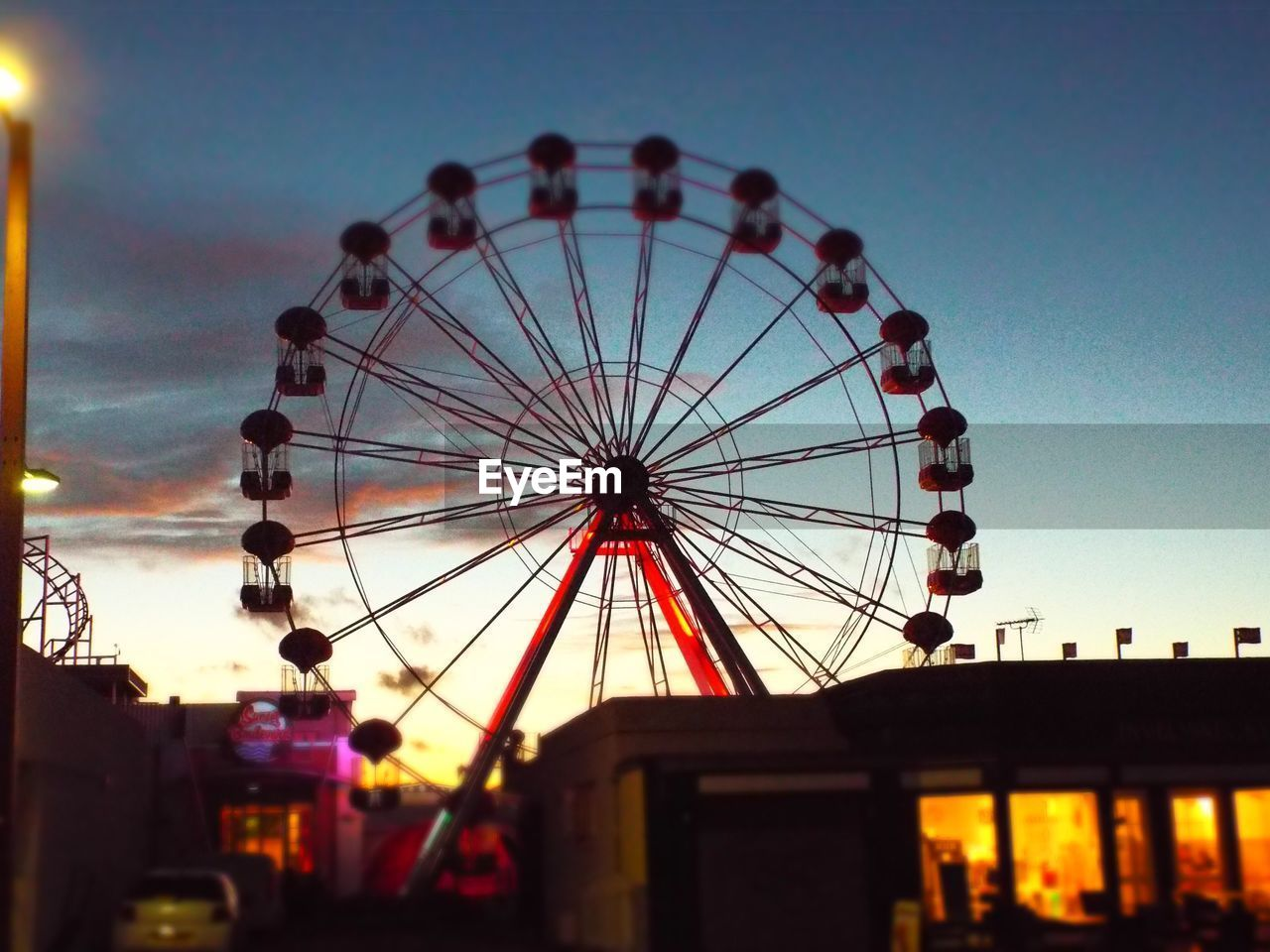 amusement park, ferris wheel, arts culture and entertainment, amusement park ride, big wheel, dusk, sunset, built structure, no people, outdoors, low angle view, sky, clear sky, silhouette, building exterior, architecture, night, illuminated, carousel