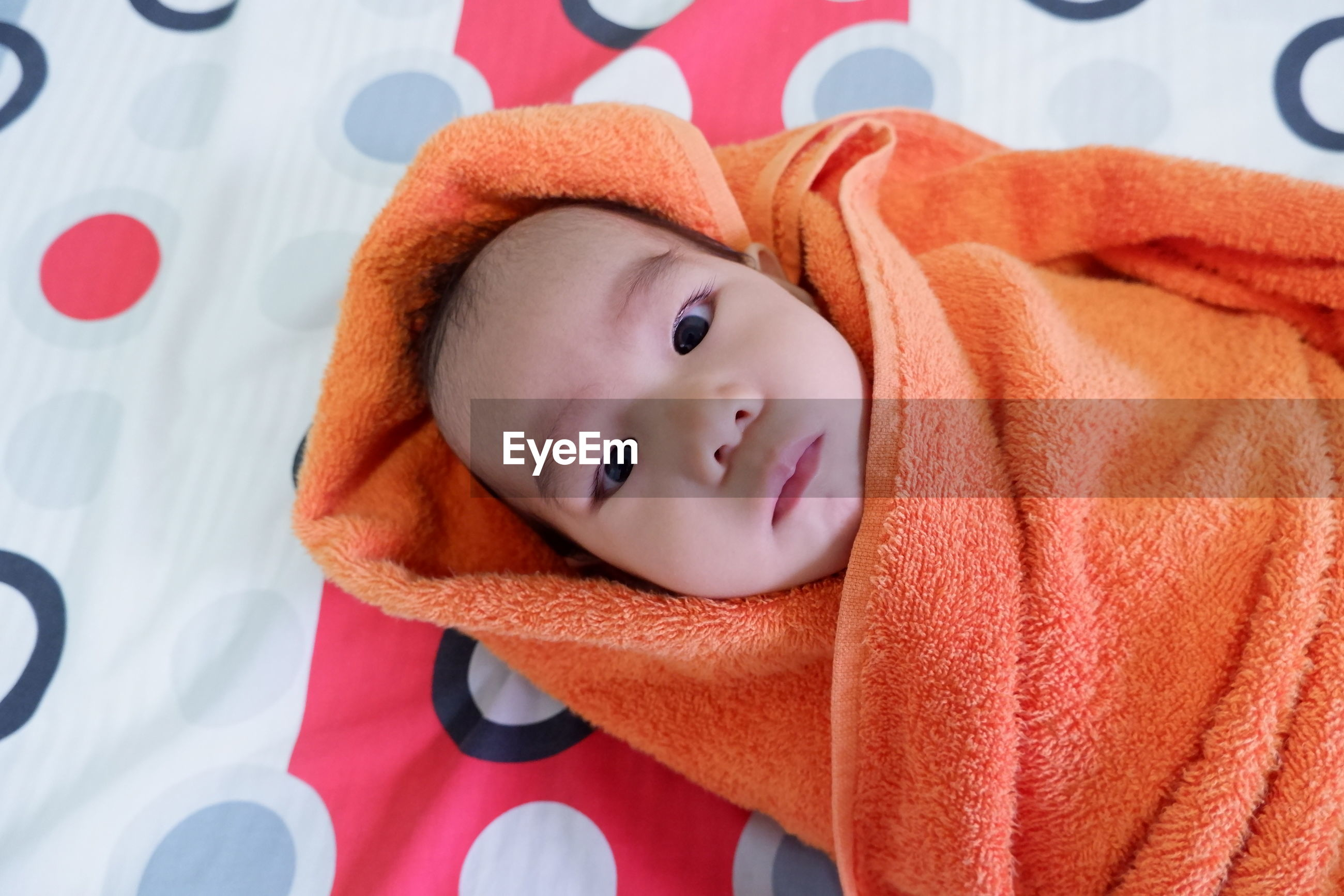 High angle portrait of cute baby wrapped in blanket lying on bed at home