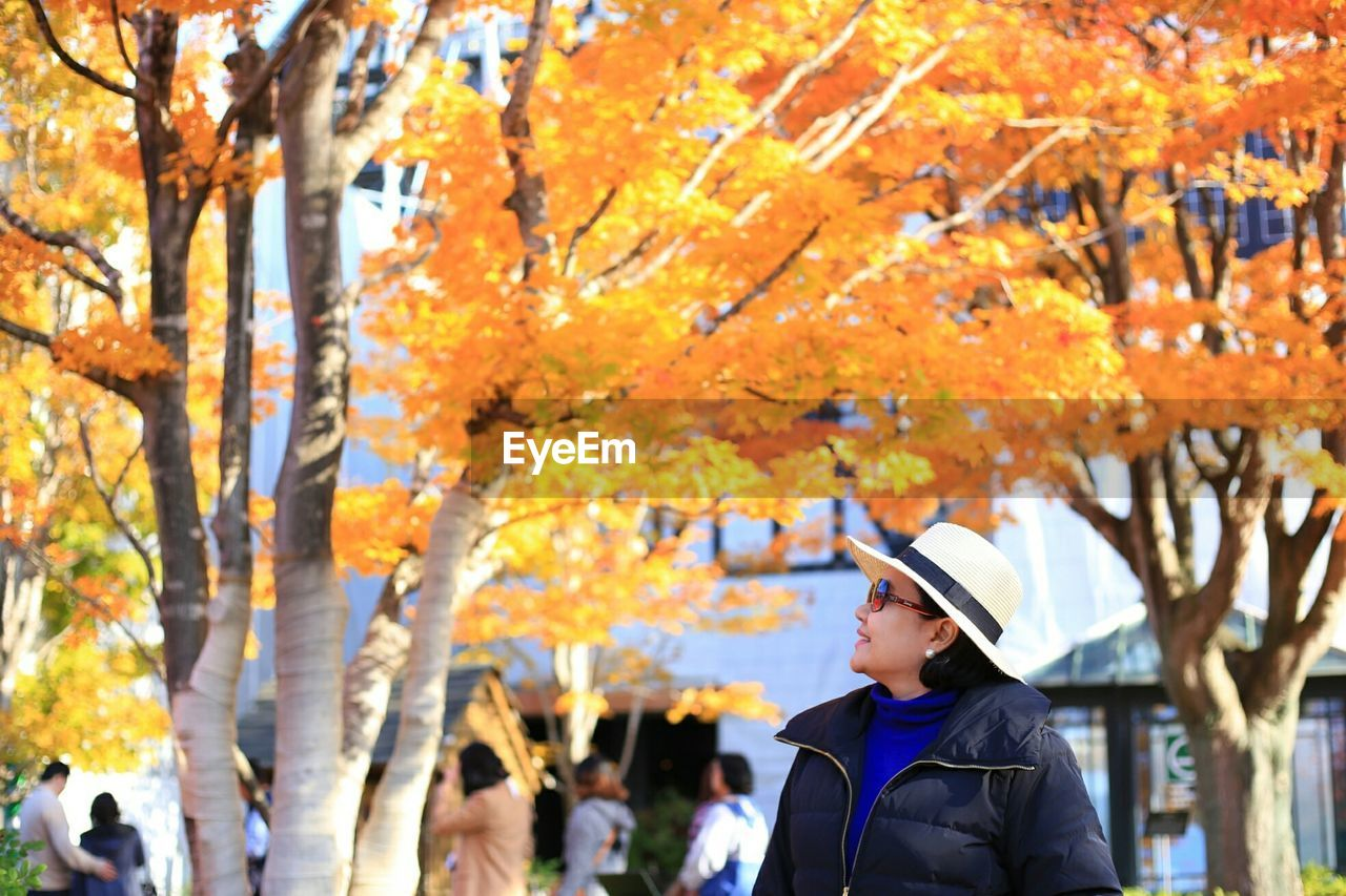 Woman Standing By Tree At Park During Autumn
