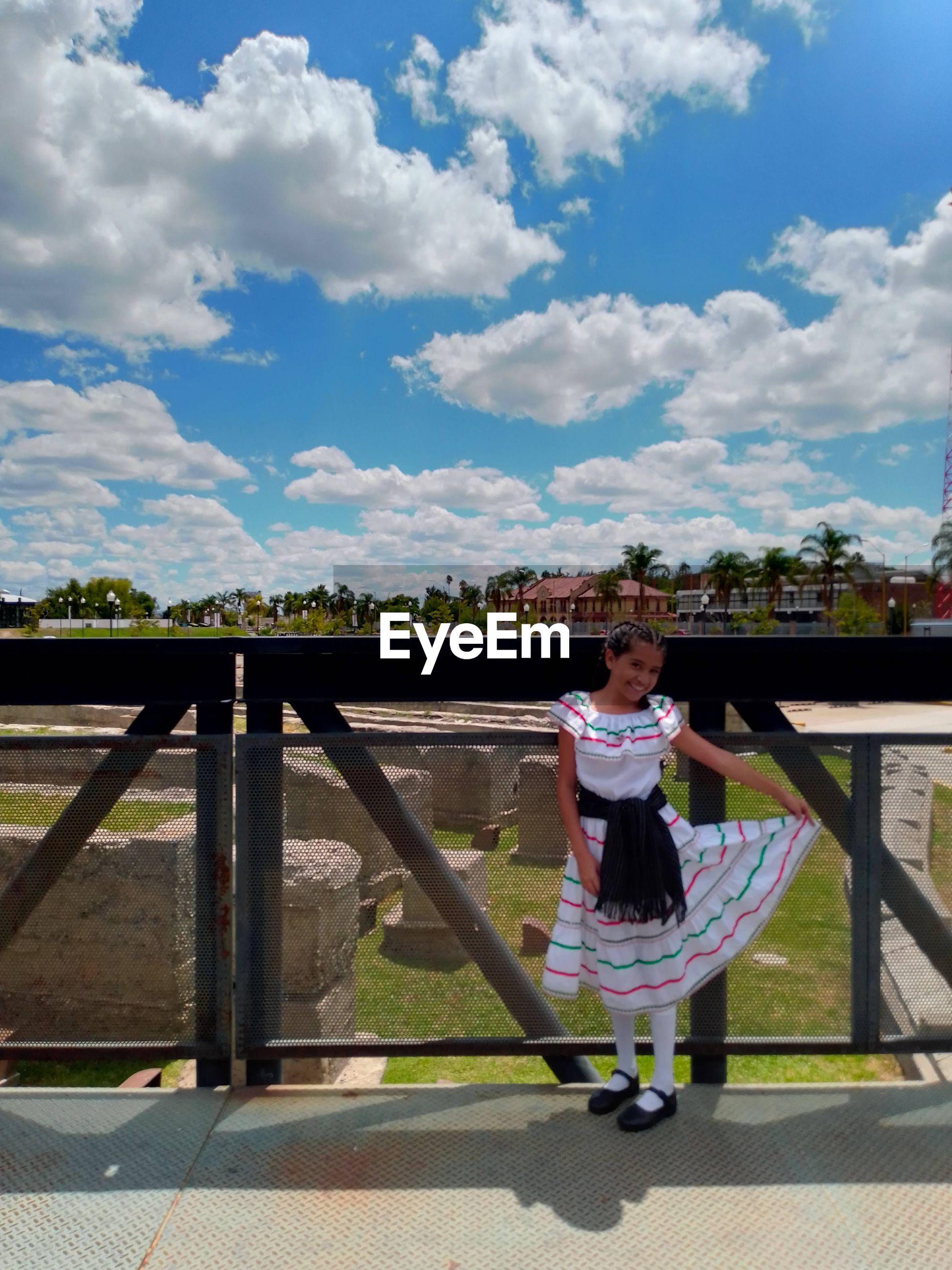 Full length of girl standing against sky latino girl on mexican revolution dress.