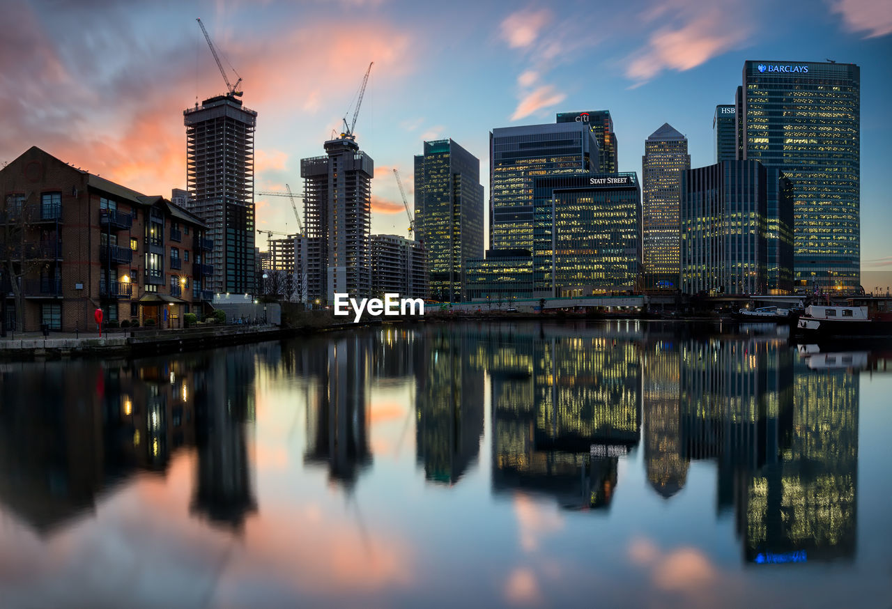 Reflection of buildings in river against sky during sunset