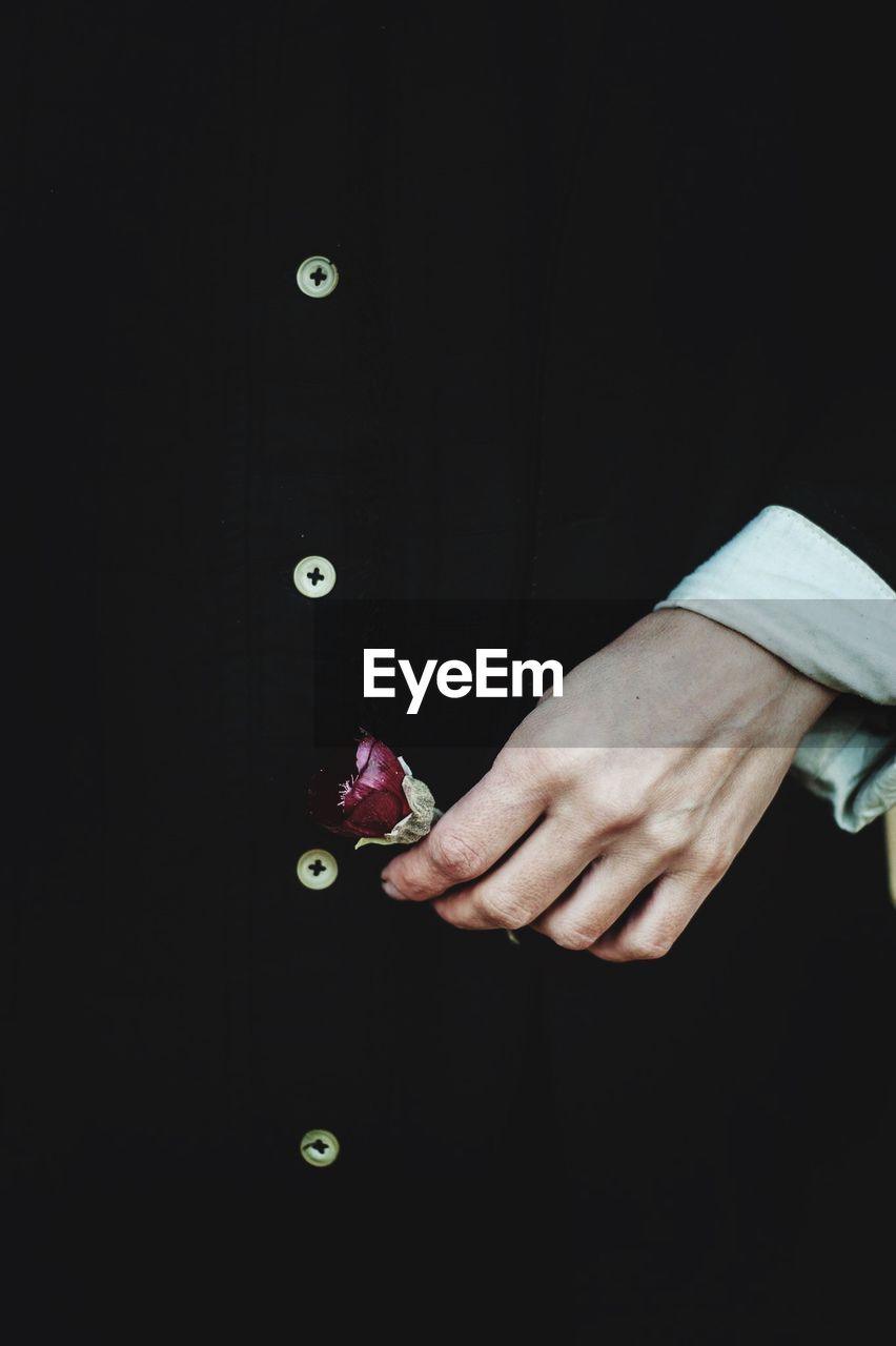 one person, human hand, hand, indoors, human body part, black background, real people, copy space, men, studio shot, lifestyles, holding, midsection, body part, leisure activity, standing, business, well-dressed, suit, finger
