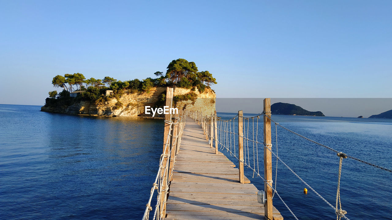 water, sky, sea, scenics - nature, beauty in nature, clear sky, tranquility, tranquil scene, nature, blue, plant, tree, no people, land, day, idyllic, railing, non-urban scene, beach, outdoors