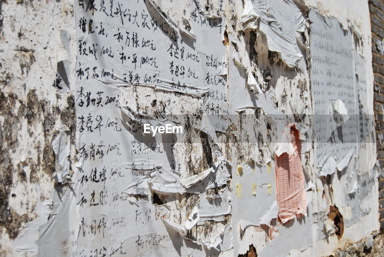 communication, text, wall - building feature, torn, no people, damaged, old, weathered, paper, hanging, script, poster, non-western script, day, architecture, peeling off, built structure, western script, outdoors, decline, deterioration, ruined, message