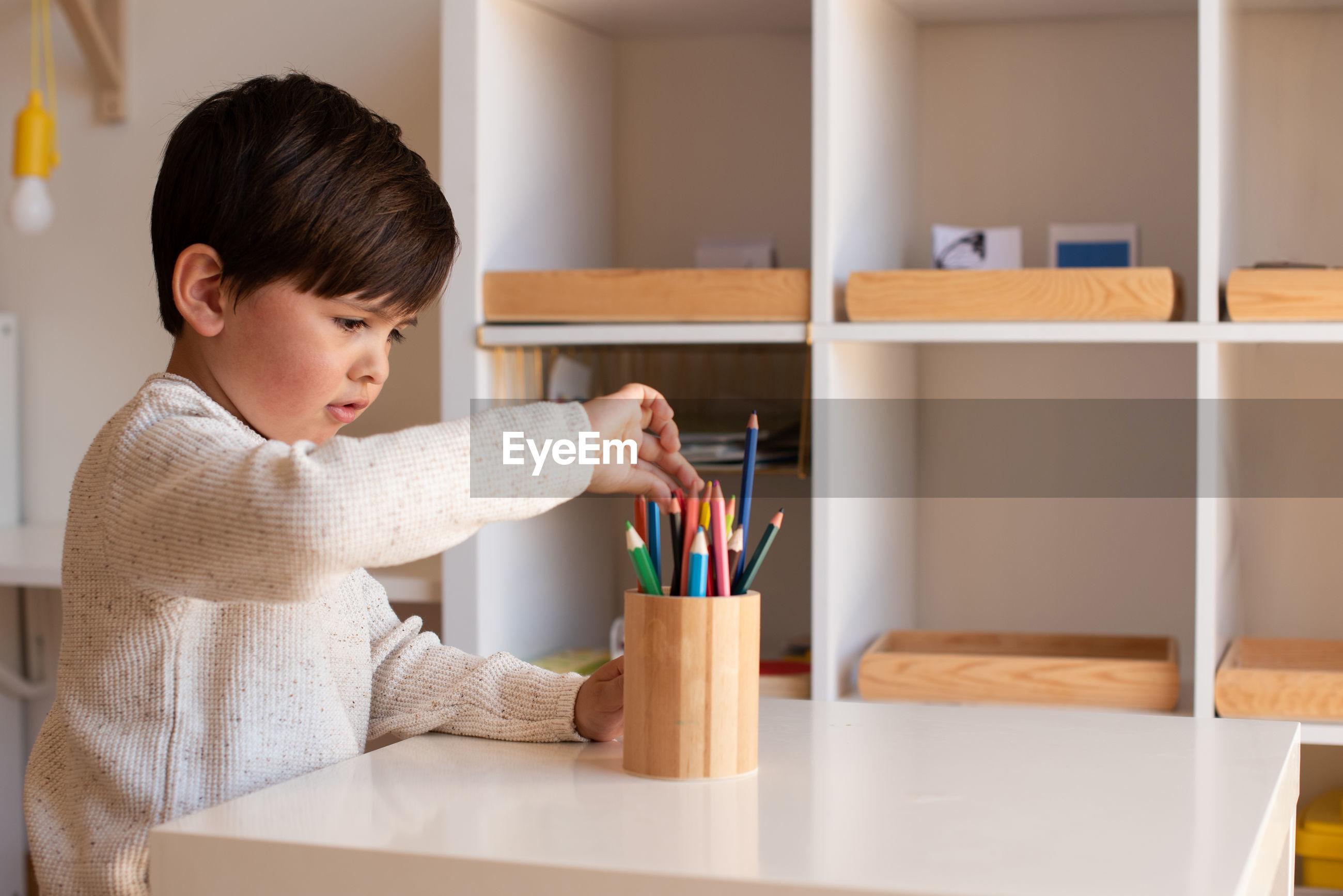 FULL LENGTH OF BOY HOLDING TABLE