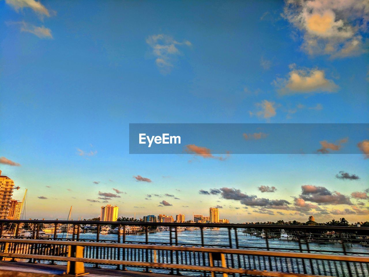 sky, railing, built structure, water, architecture, cloud - sky, bridge - man made structure, outdoors, river, no people, day, blue, building exterior, nature, sunset, city