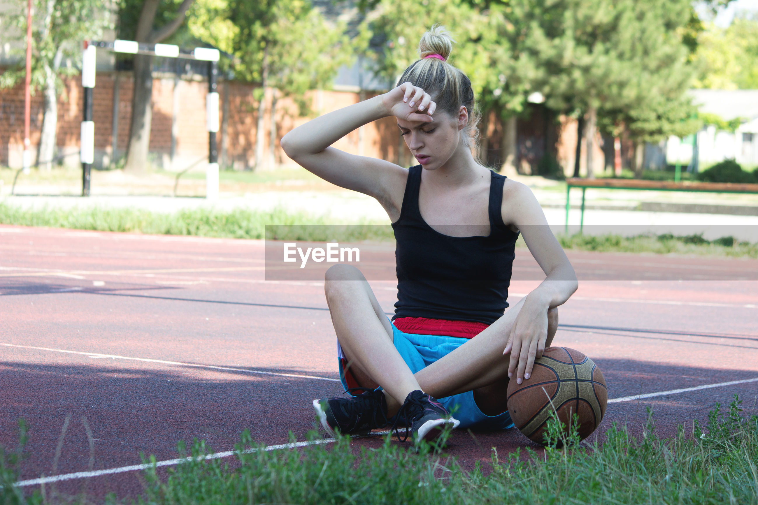 Full length of woman with basketball sitting outdoors