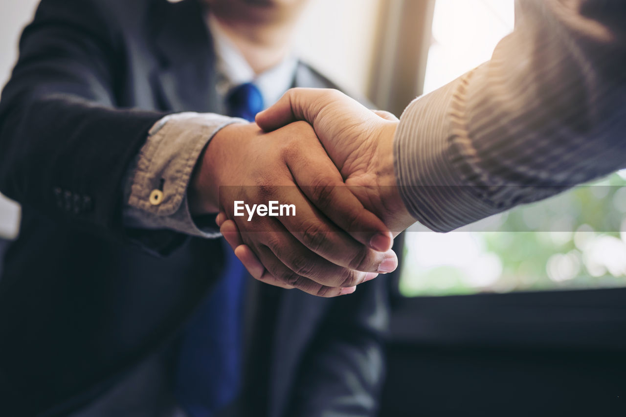 Cropped image of colleagues shaking hands in office