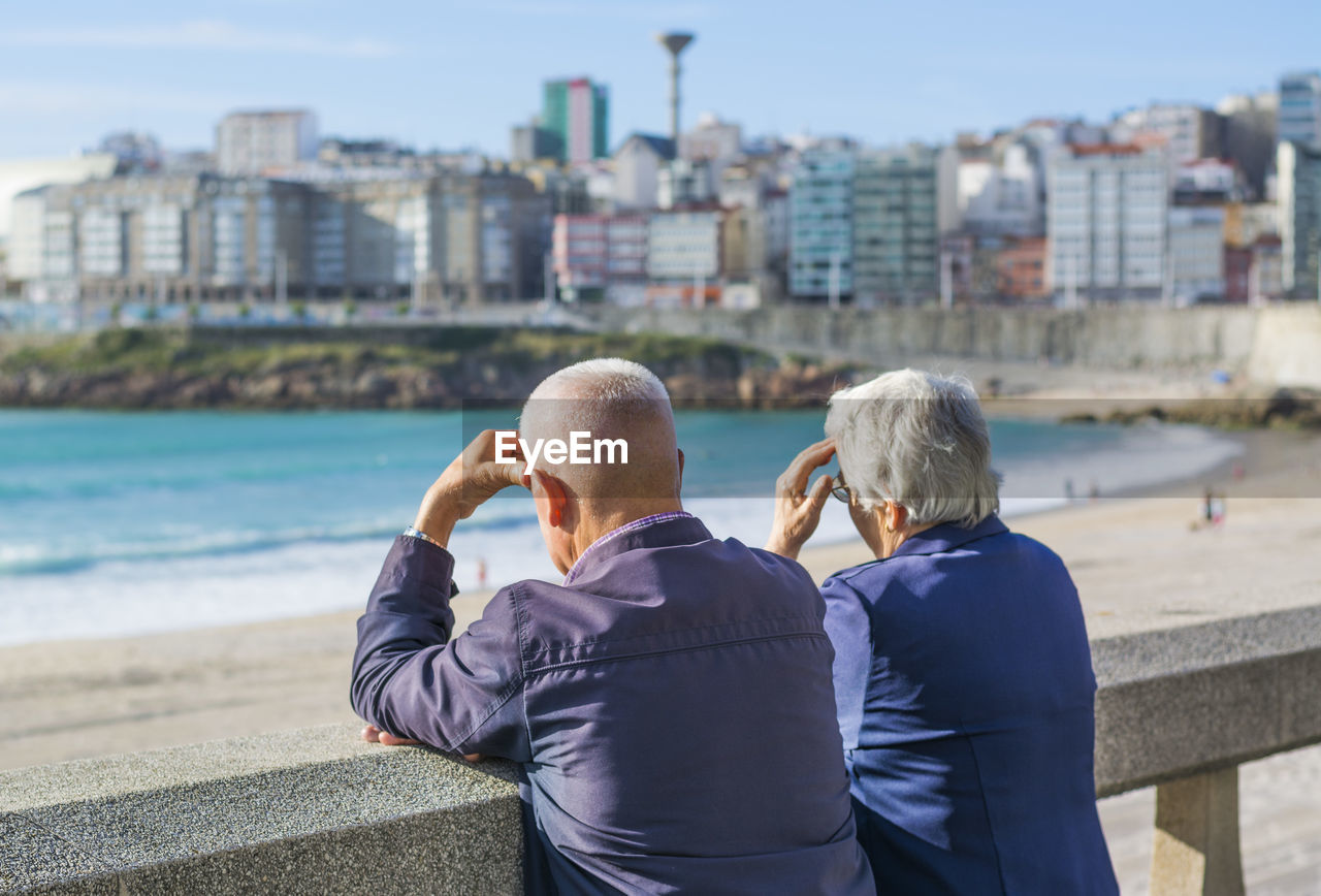 Rear view of senior couple standing by retaining wall at beach during sunny day
