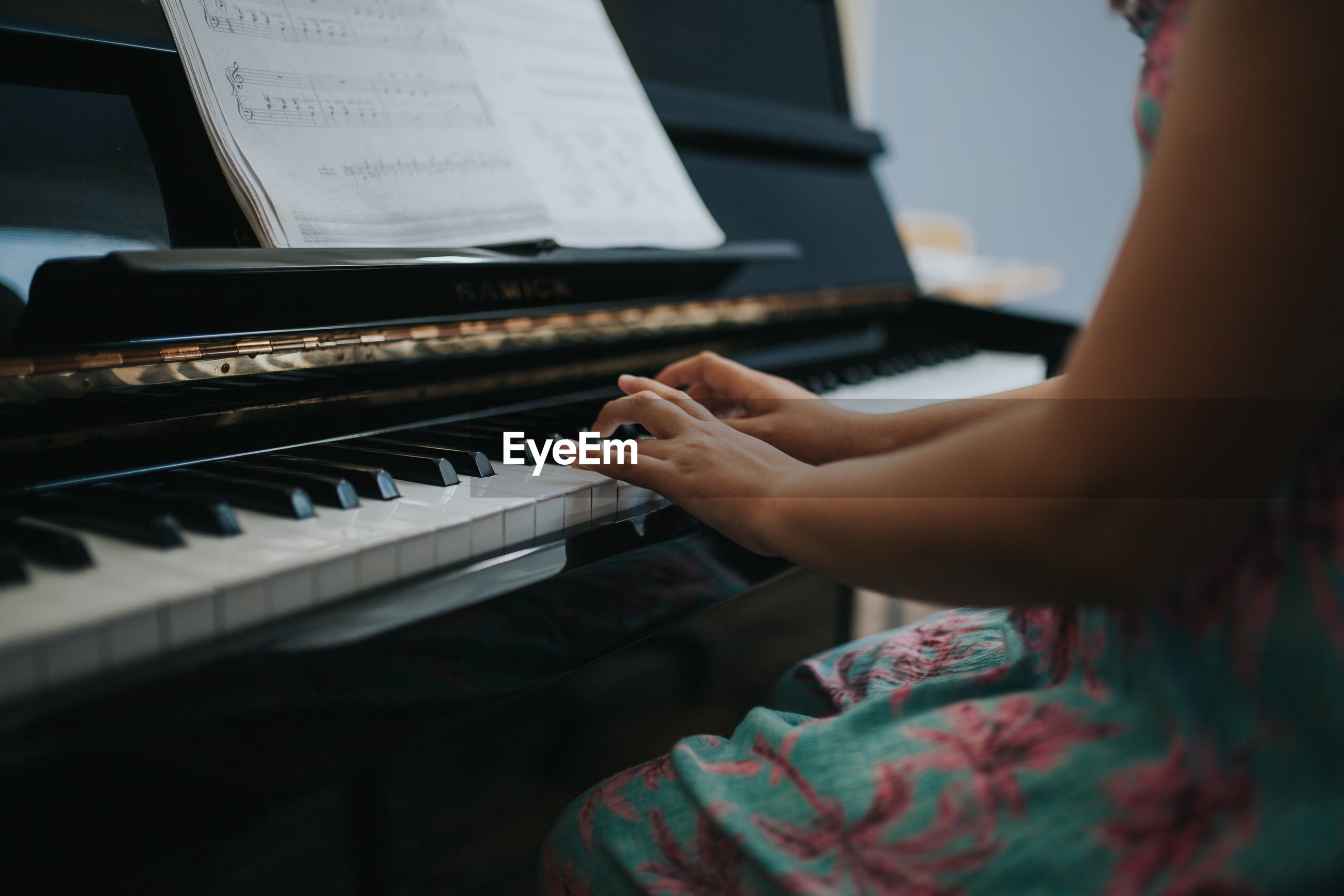 Midsection of girl wearing dress while playing piano