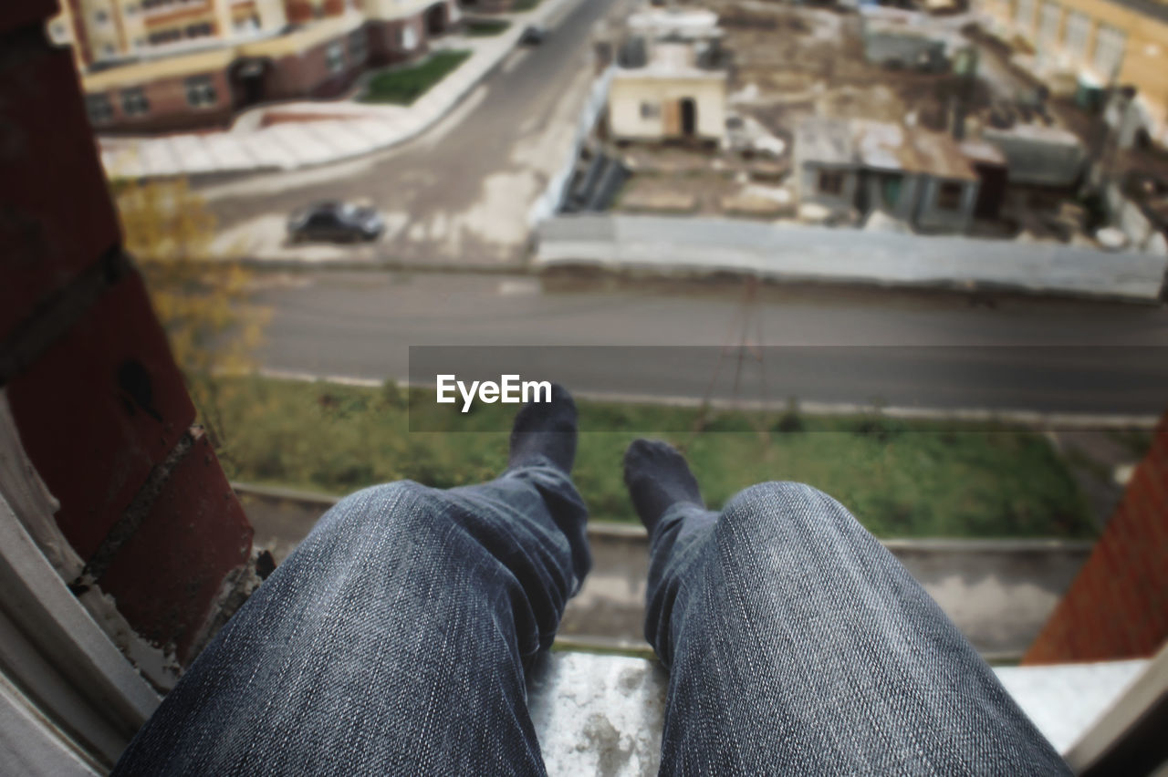 human leg, human body part, real people, personal perspective, lifestyles, one person, body part, jeans, low section, day, unrecognizable person, men, transportation, casual clothing, sitting, high angle view, focus on foreground, leisure activity, architecture, outdoors, sock, human foot