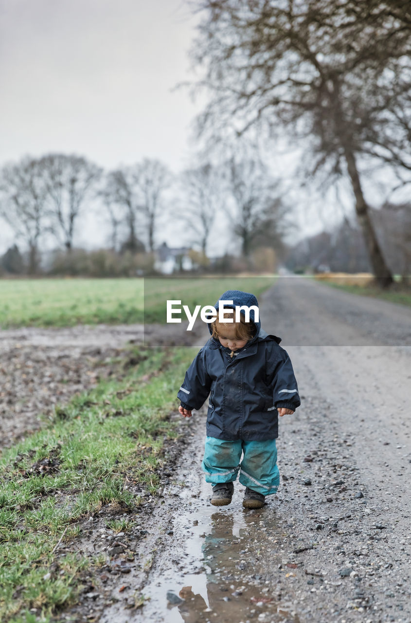 childhood, child, one person, males, boys, front view, full length, men, plant, real people, nature, clothing, day, land, field, leisure activity, tree, casual clothing, winter, warm clothing, innocence, outdoors, hood - clothing