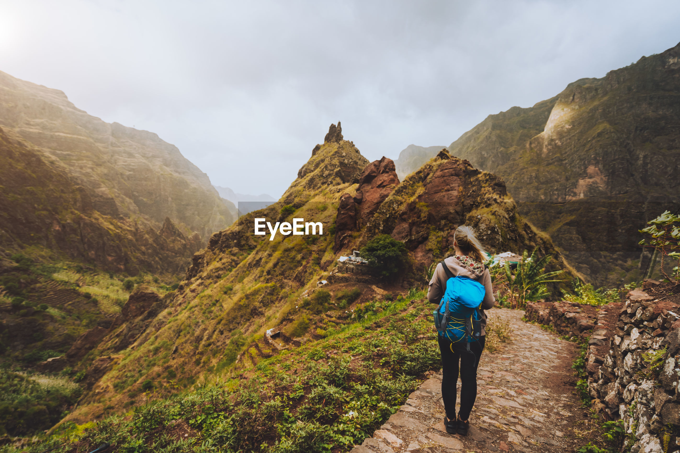 Rear view of woman walking on trail against mountains