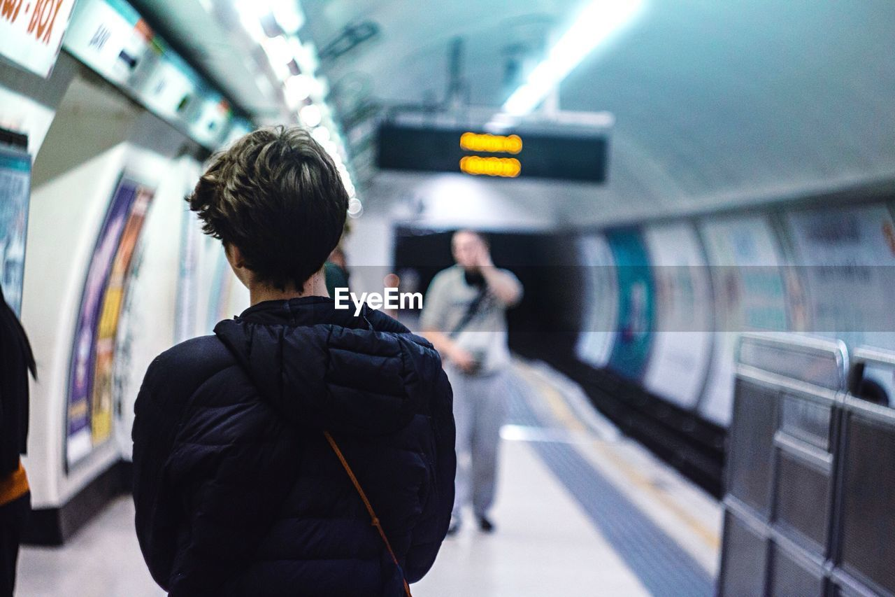 Rear View Of Woman Standing At Underground Subway Platform
