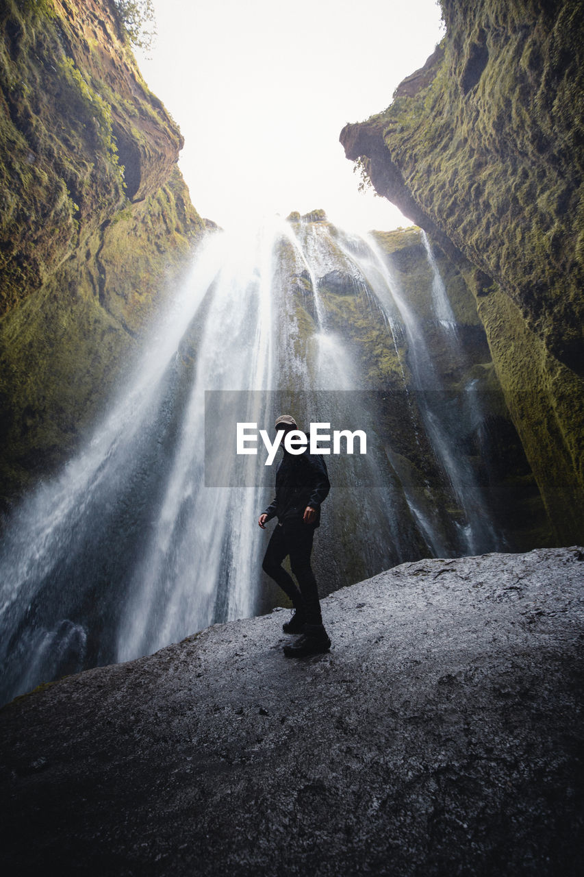 MAN STANDING BY WATERFALL