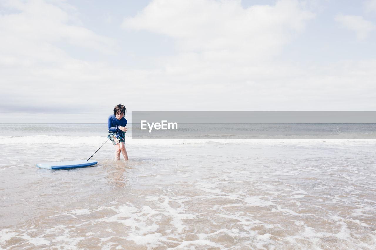 Full length of child on beach against sky
