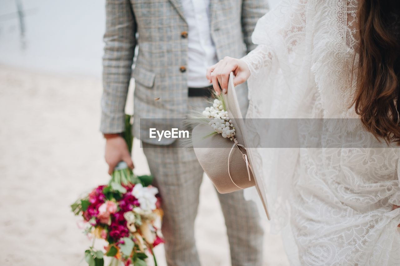 Midsection Of Bride With Bridegroom Holding Hat