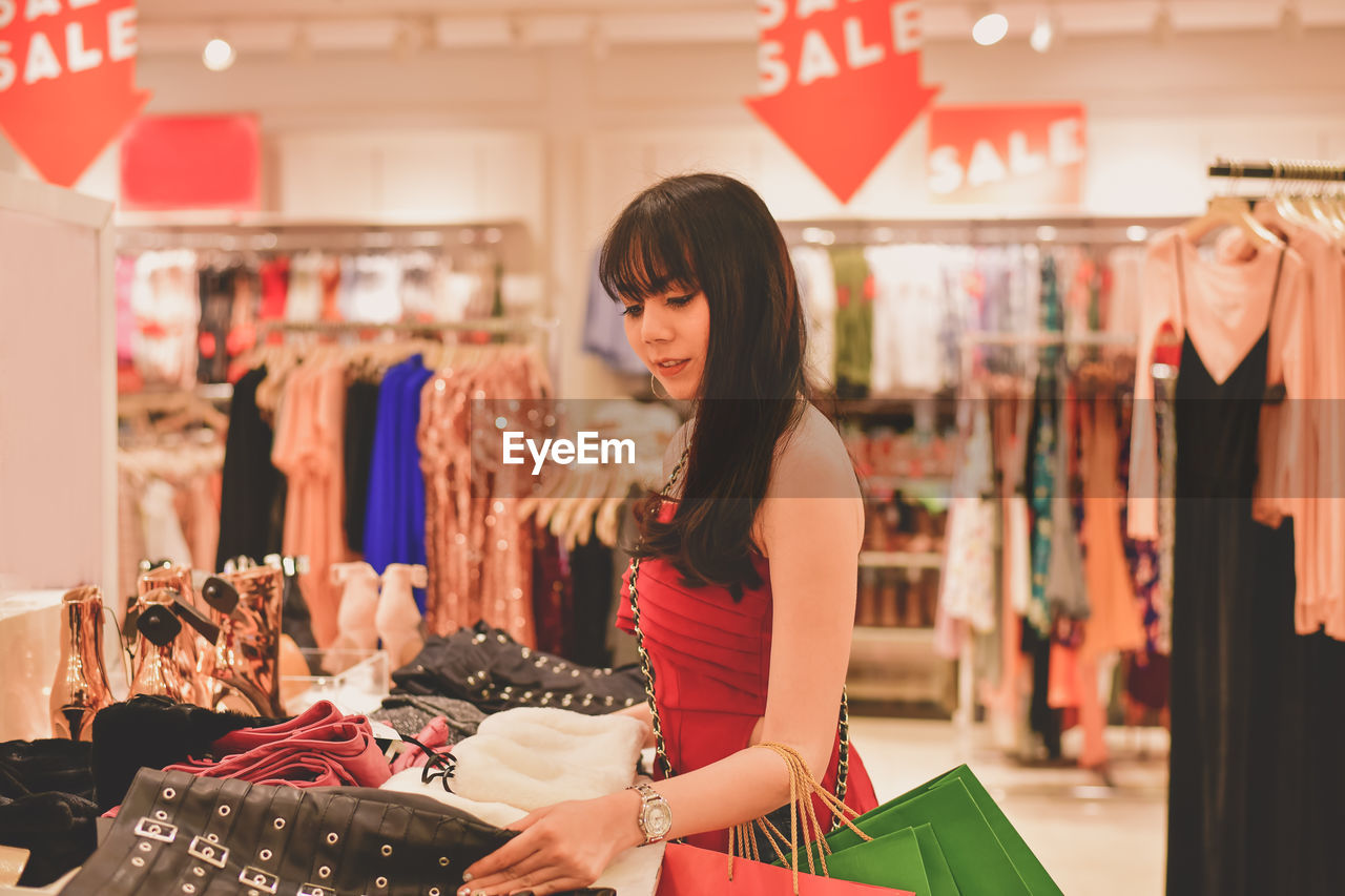 Young Woman Buying Clothes In Shopping Mall