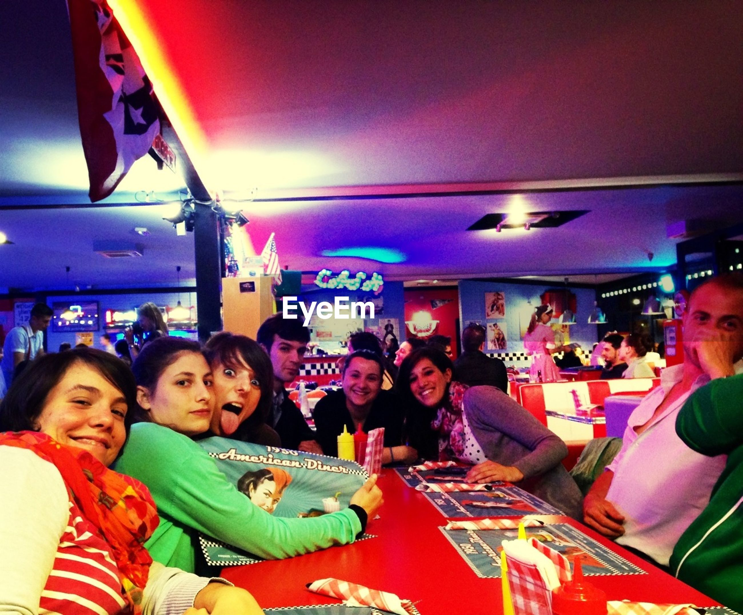 indoors, lifestyles, illuminated, leisure activity, large group of people, enjoyment, togetherness, fun, celebration, sitting, men, person, night, happiness, arts culture and entertainment, lighting equipment, casual clothing, retail
