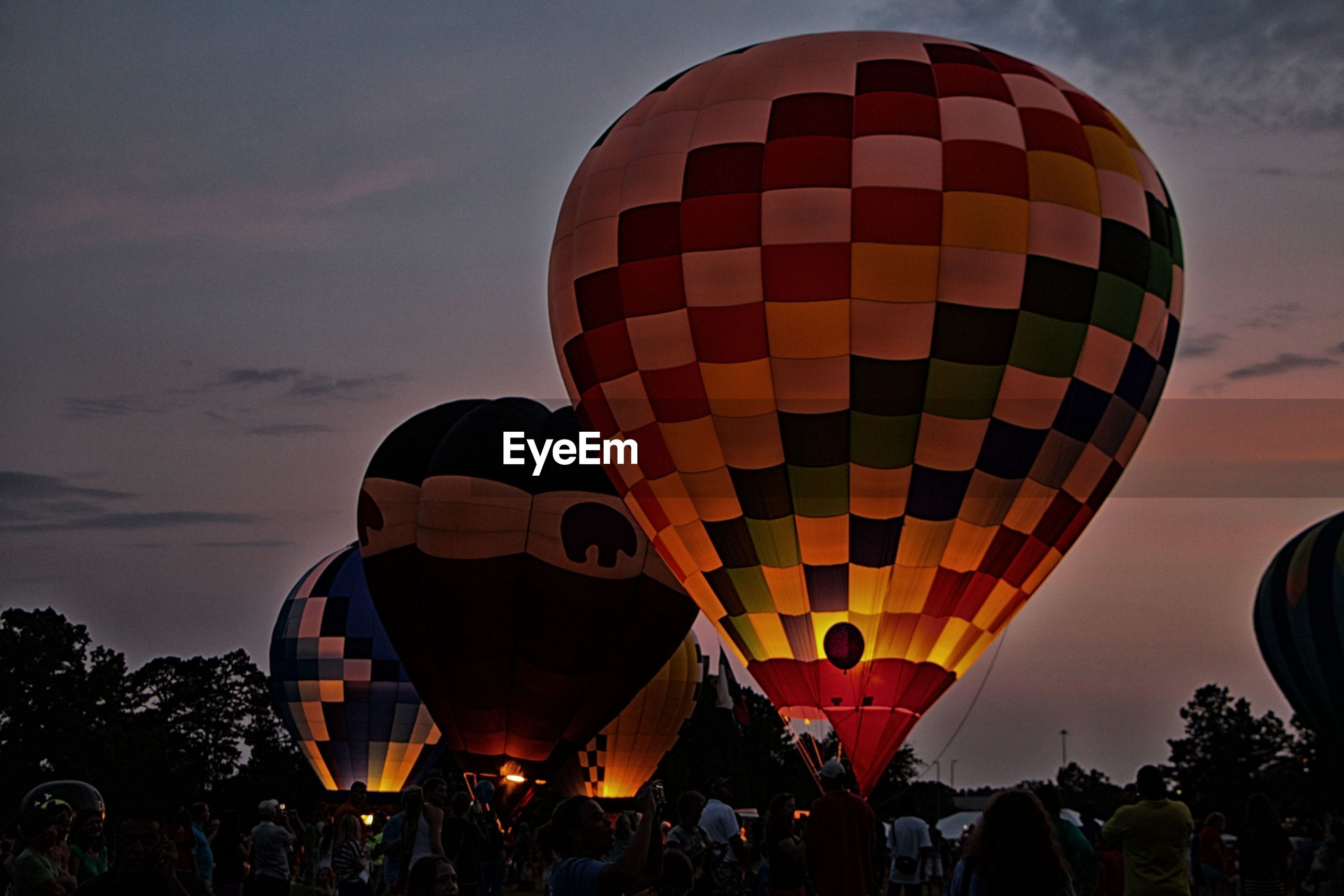 Low angle view of people by colorful hot air balloons against sky