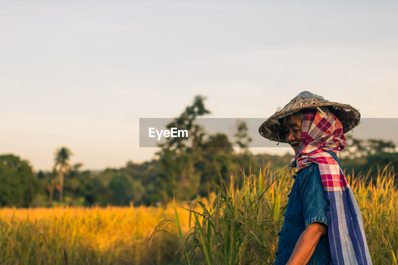 Side View Of Senior Woman Standing On Grassy Field Against Clear Sky During Sunset