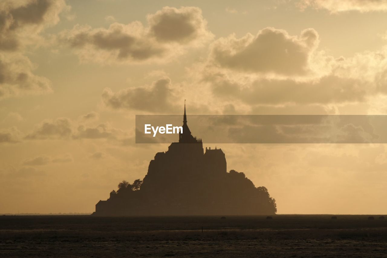 Mont saint-michel against cloudy sky during sunset