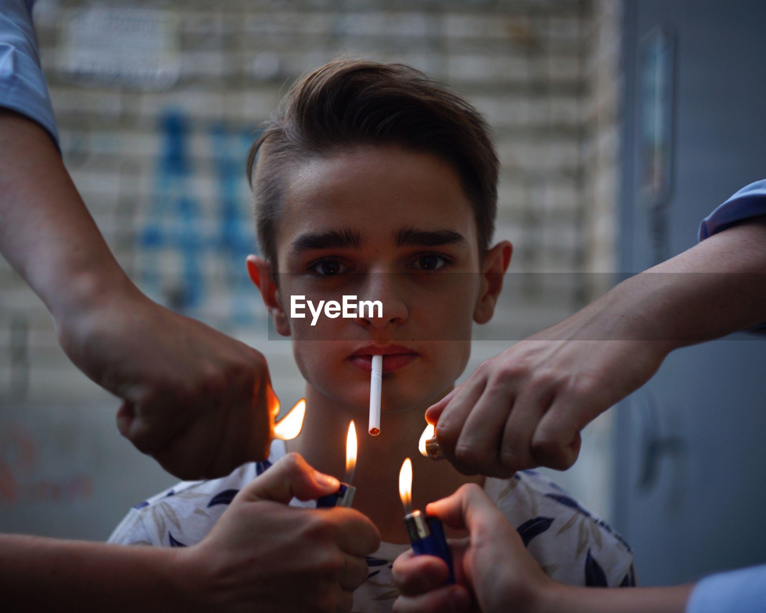Hands igniting cigarette of teenage boy
