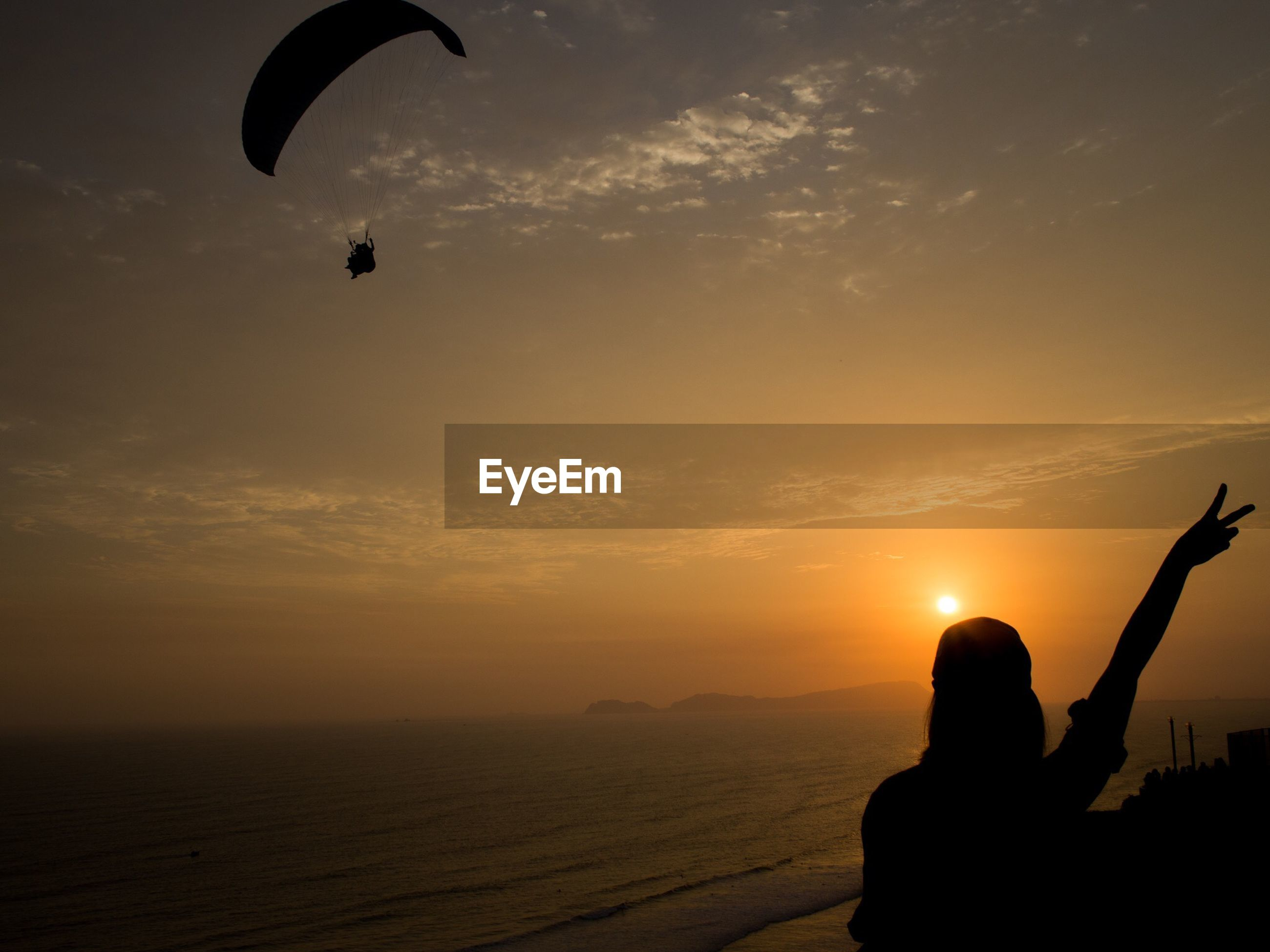 Silhouette woman with person paragliding over sea against sky during sunset