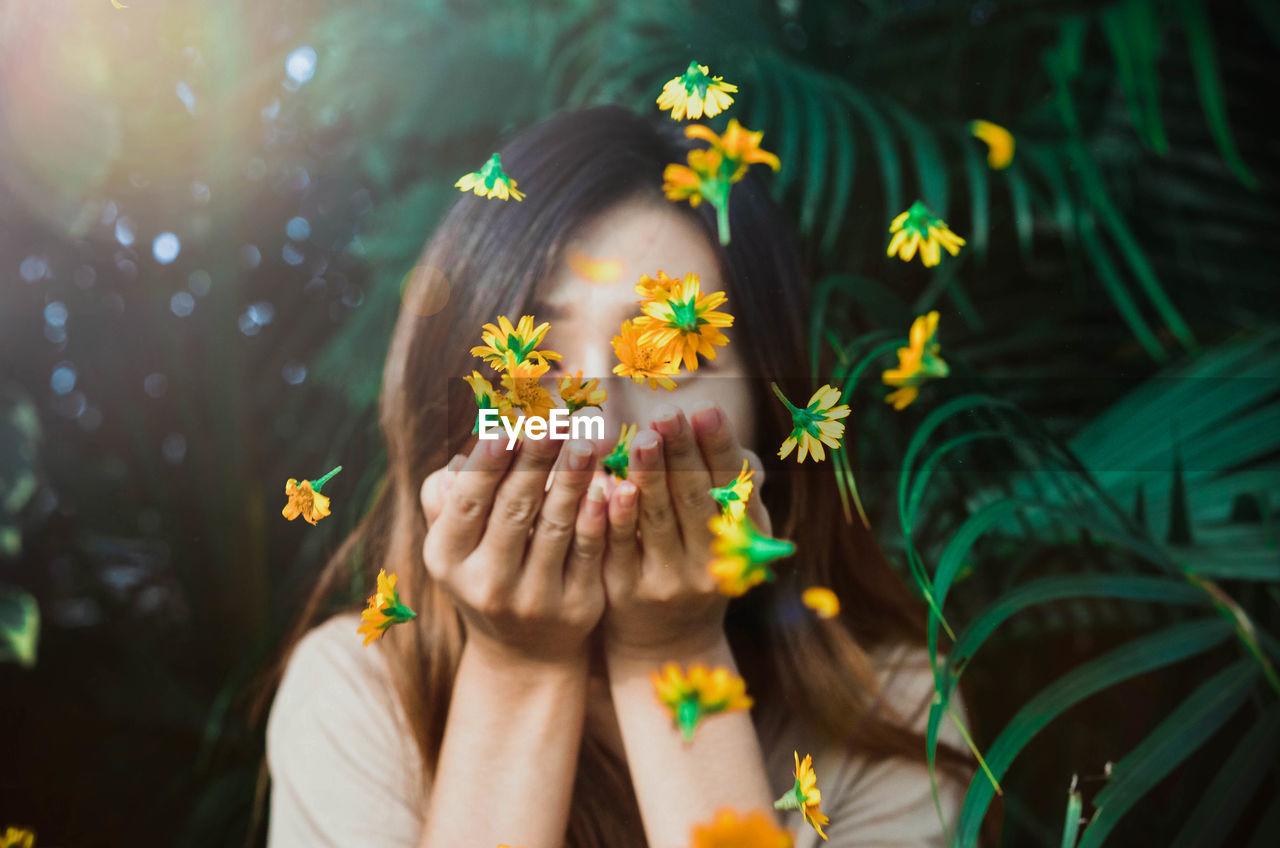 Woman blowing orange flowers
