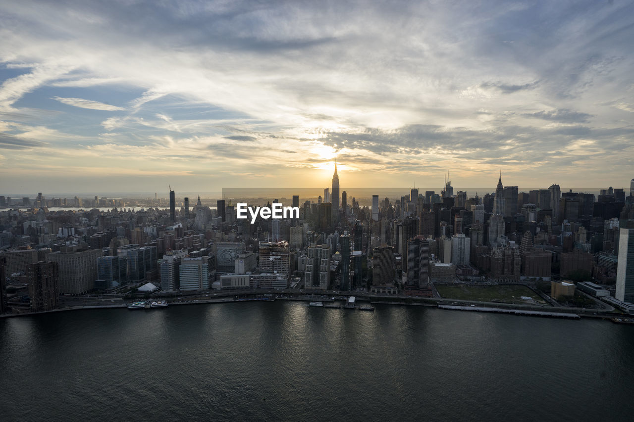Manhattan By East River Against Sky During Sunset