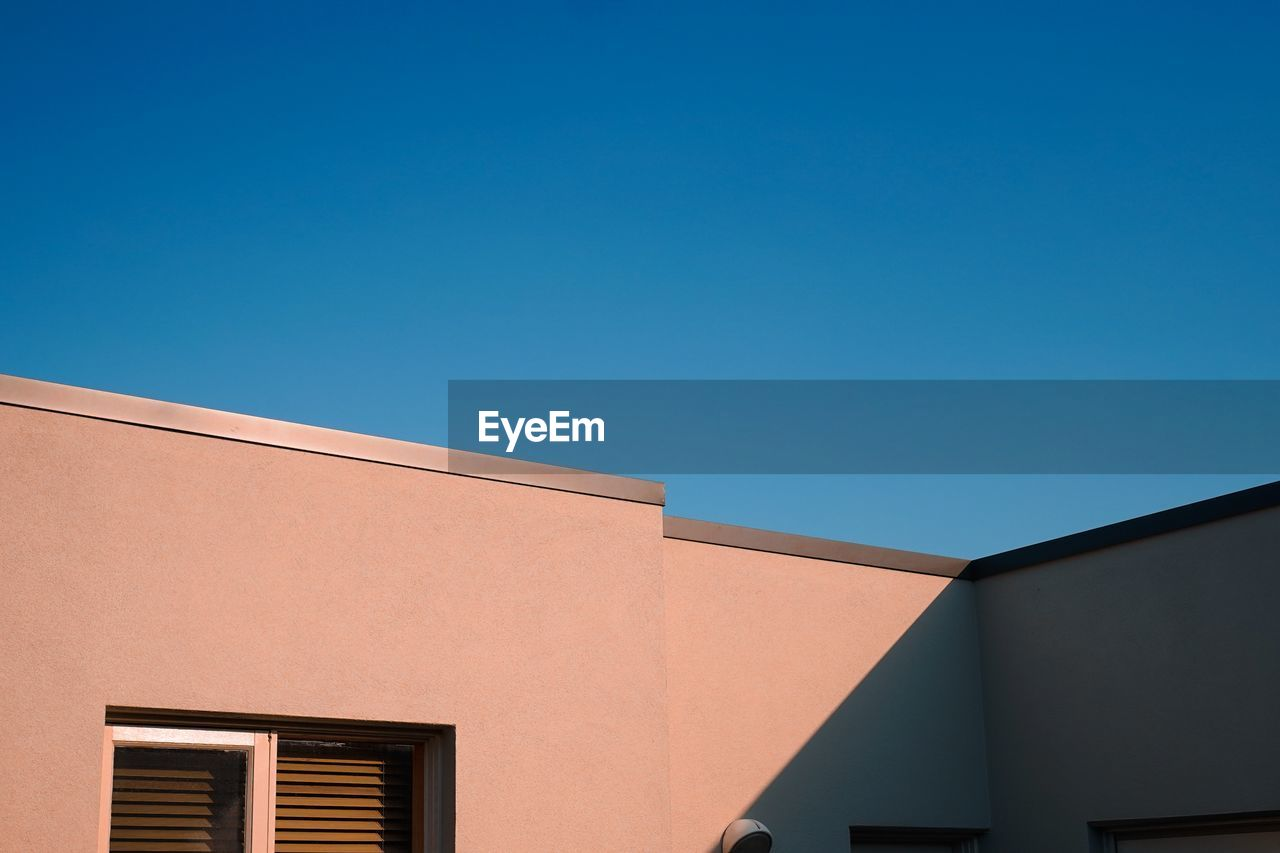built structure, architecture, building exterior, clear sky, sky, copy space, blue, low angle view, building, no people, nature, window, day, sunlight, outdoors, house, high section, residential district, wall - building feature, roof