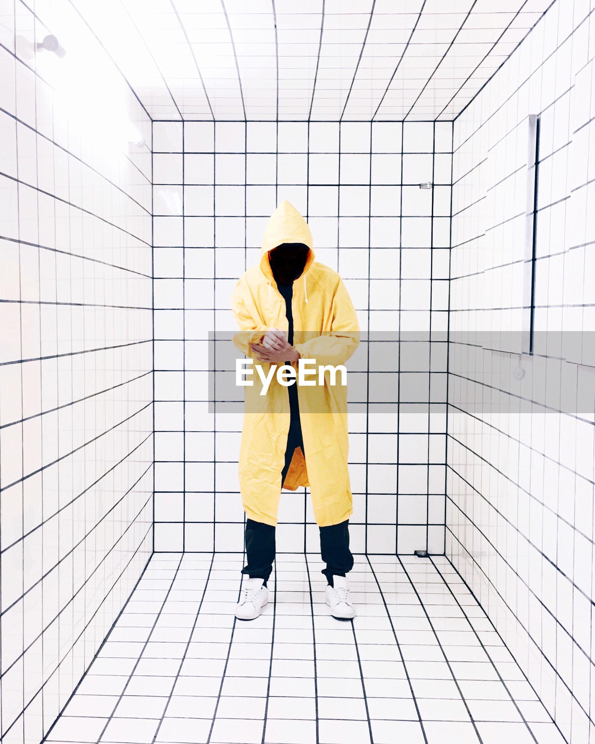 Full length of man standing on tiled floor