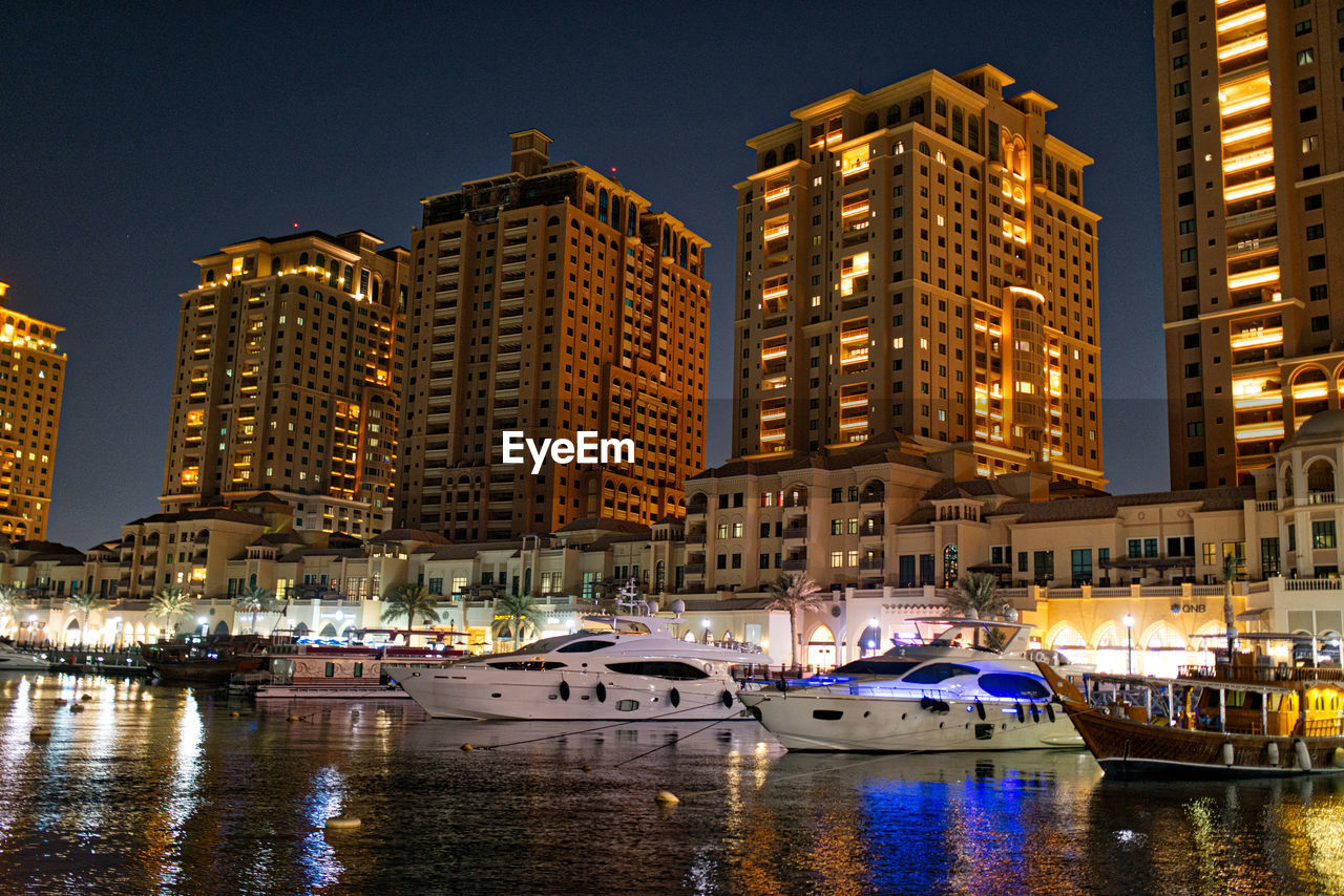 Boats Moored In River By Illuminated Modern Buildings At Night