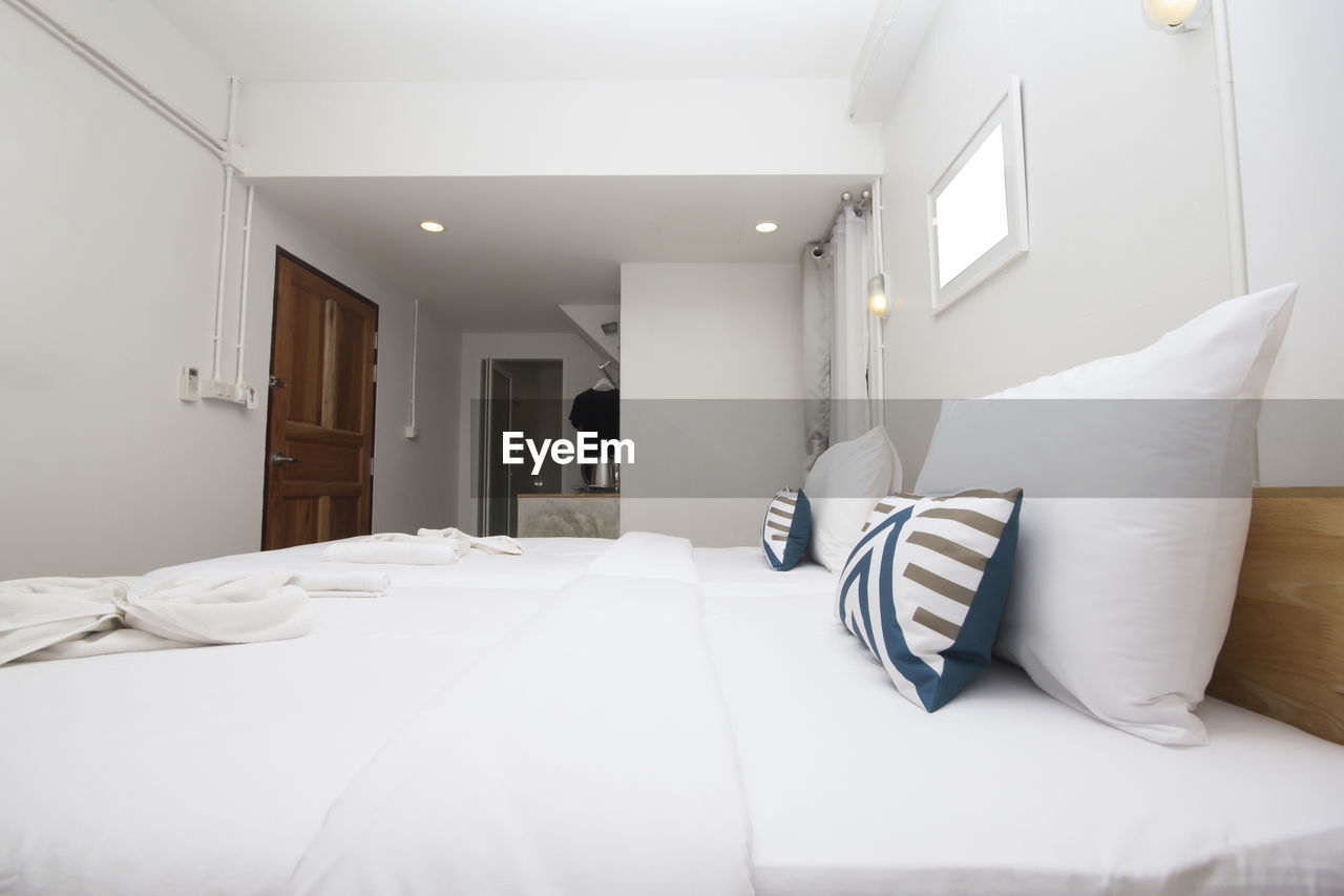 furniture, indoors, bed, white color, pillow, bedroom, domestic room, absence, home interior, no people, home showcase interior, wealth, modern, luxury, stuffed, sheet, lighting equipment, linen, hotel room, home, electric lamp, ceiling