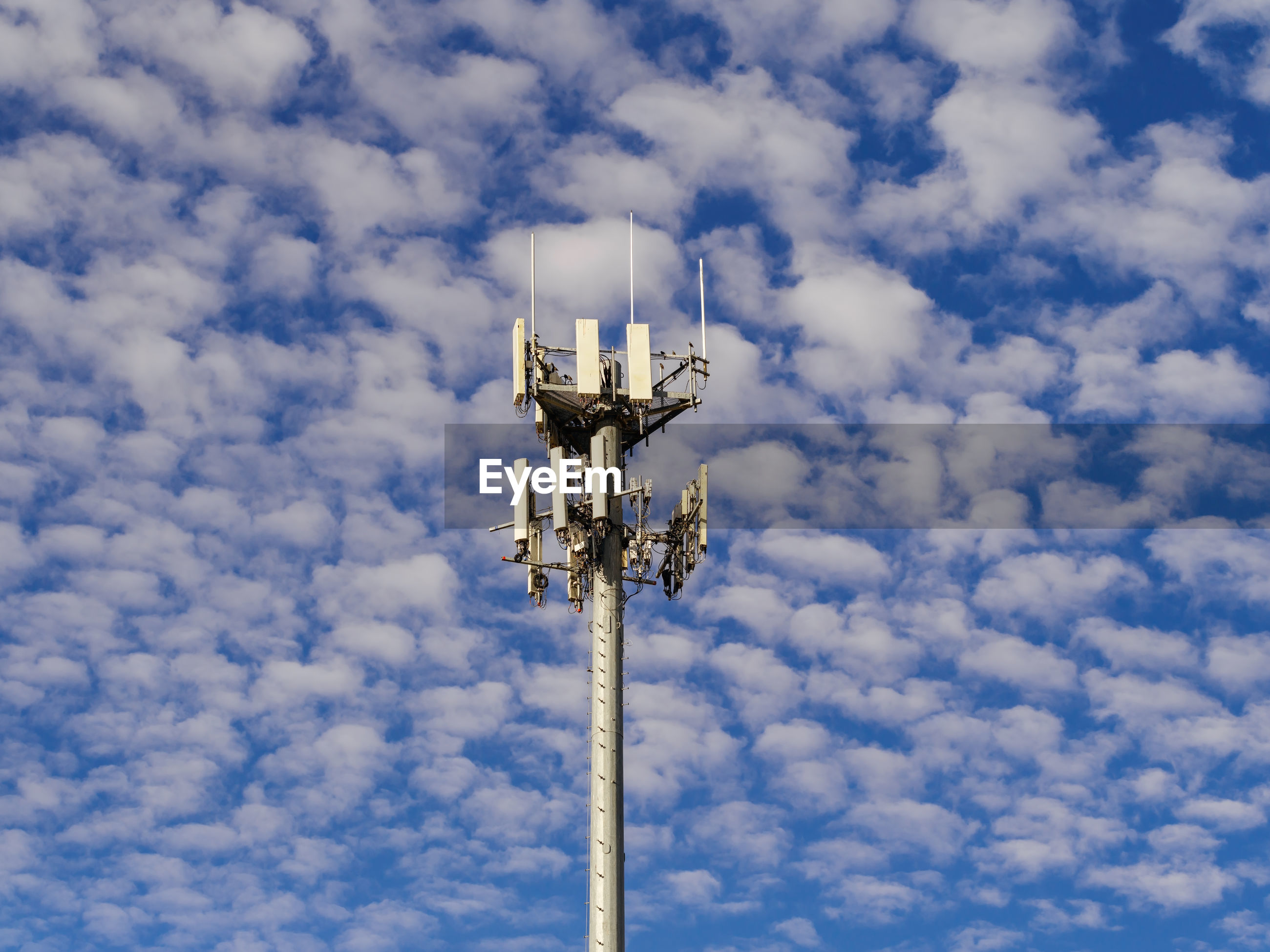 Cell phone communications tower against a partly cloudy blue sky.