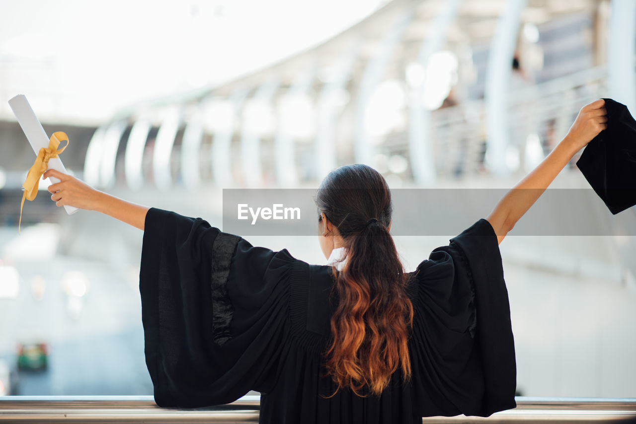 Rear view of woman with arms outstretched standing by railing
