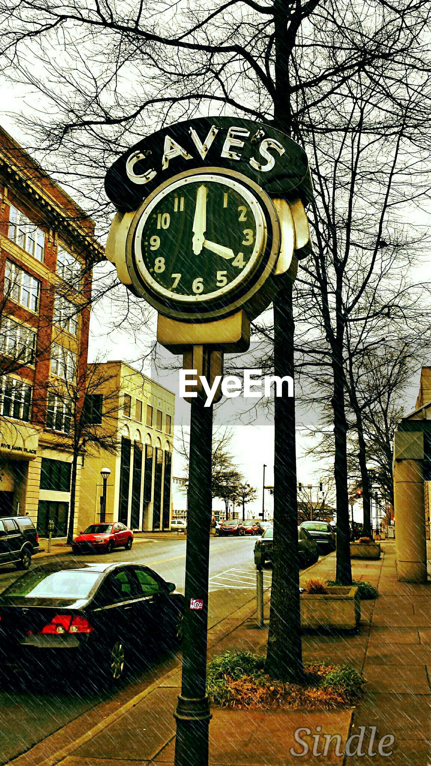 clock, text, tree, bare tree, architecture, built structure, building exterior, communication, time, western script, transportation, road sign, street, number, information sign, city, car, day, sky, clock tower