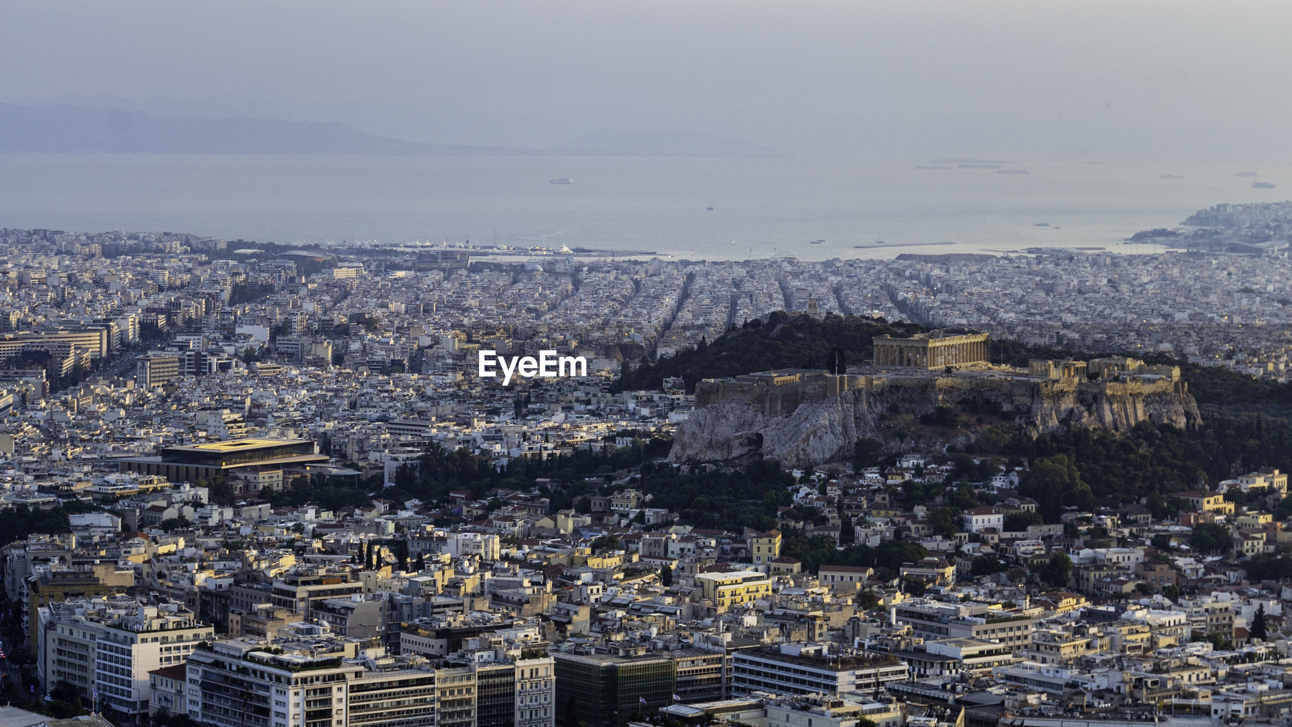 High angle view of city of athens with prominently placed acropolis against sky